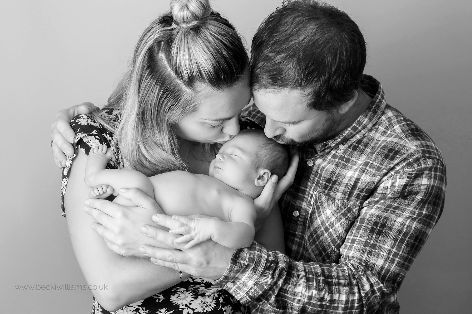 black and whtie photo of new parents holding their newborn baby boy for their photo shoot in hemel hempstead