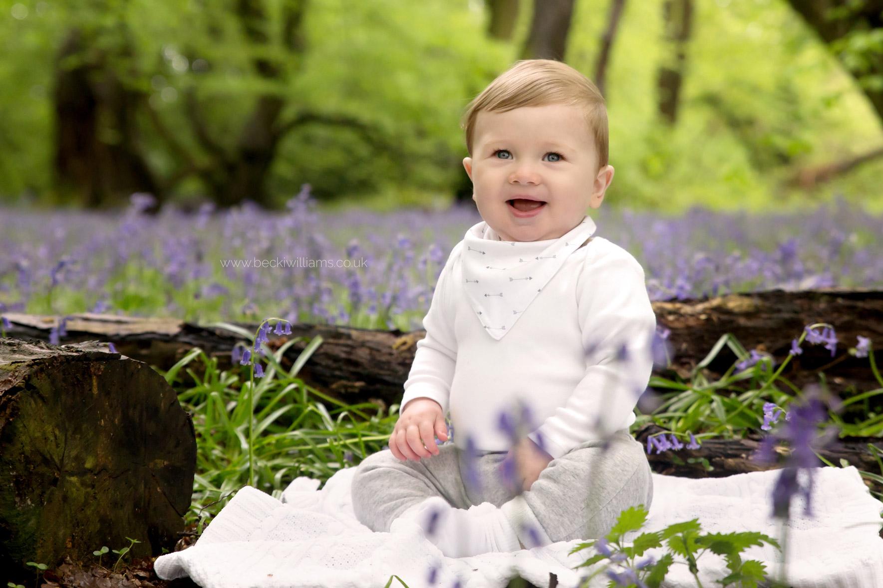 little boy sitting, smiling amongst the bluebells in st albans