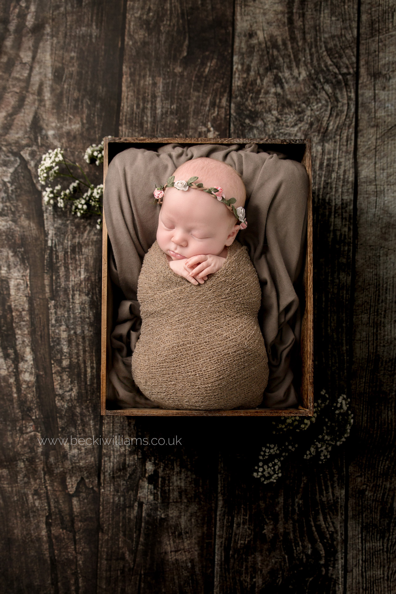 newborn girl laying in a brown crate with a flower headband for her newborn photo shoot in hemel hempstead