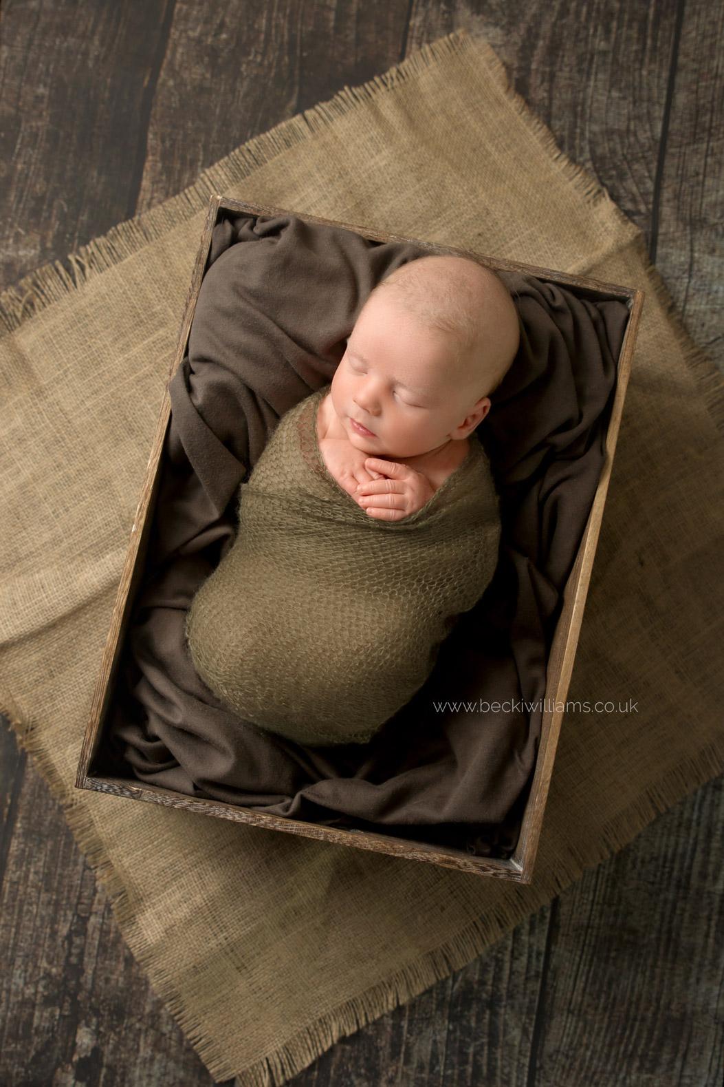 newborn-photography-hemel-hempstead-crate-brown-wrapped-sleeping.jpg