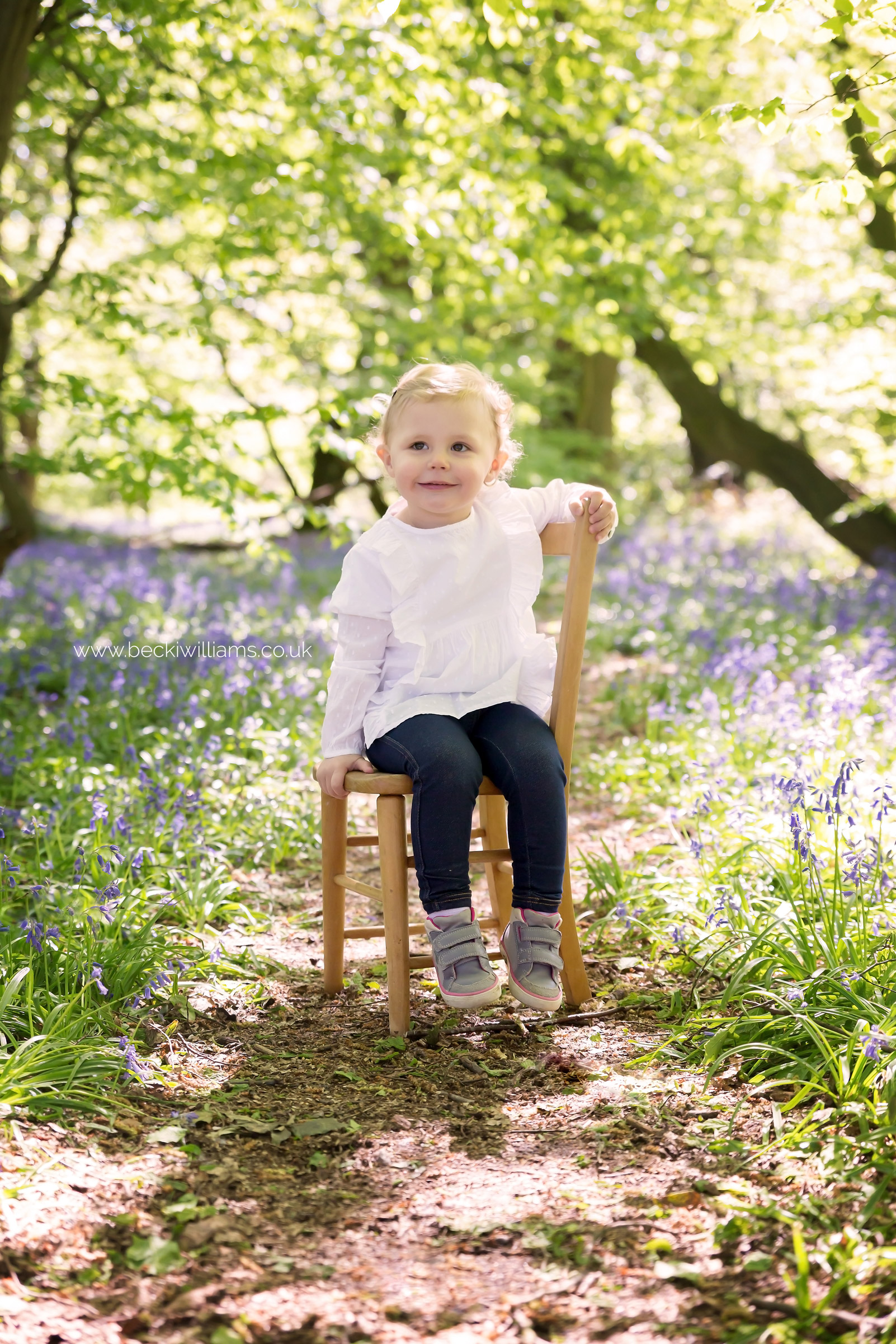 little girl sitting on a chair amongst the bluebells