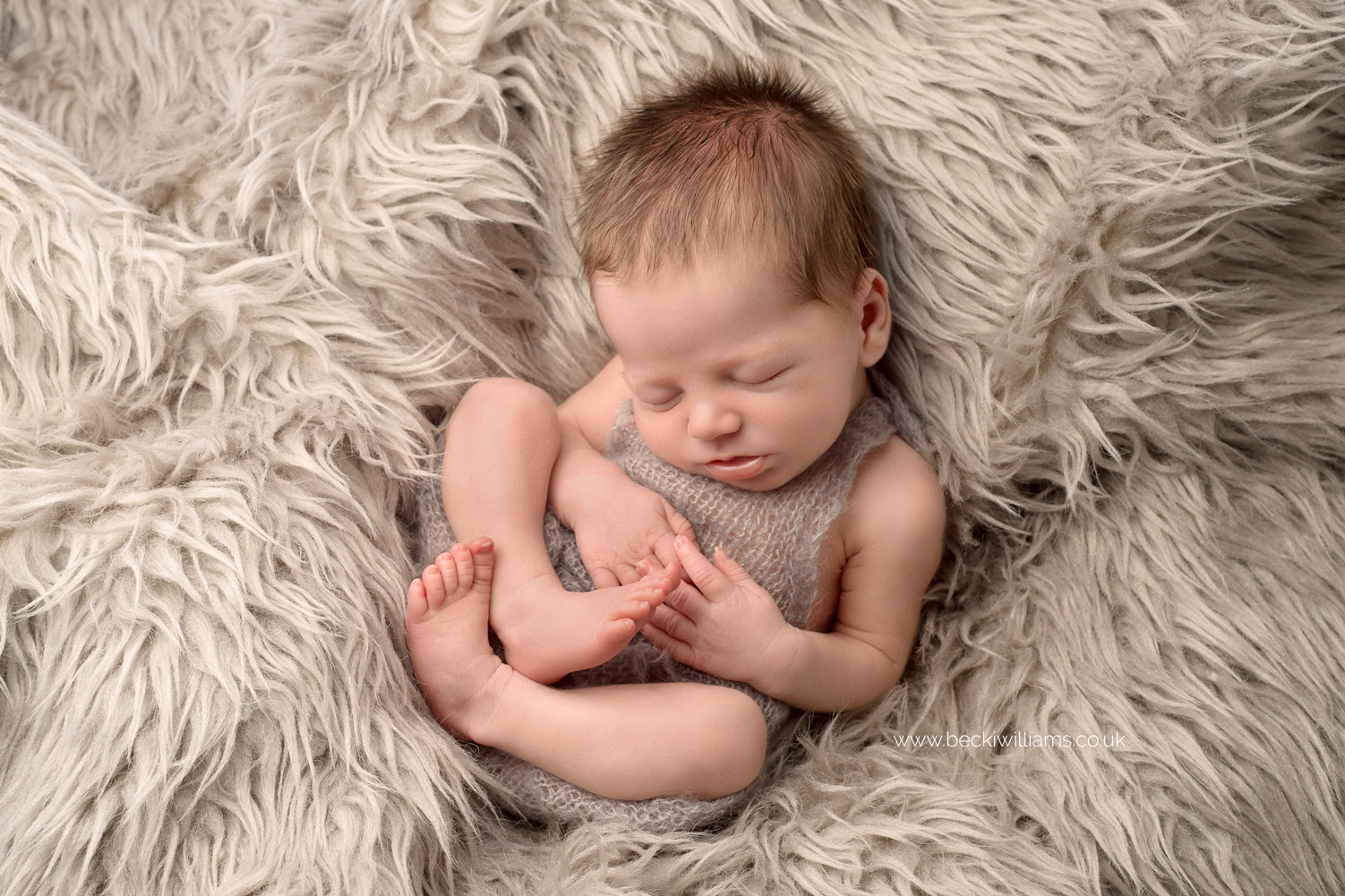 newborn boy lays sleeping on a grey furry blanket, wearing a grey romper for his newborn photo shoot in hemel hempstead