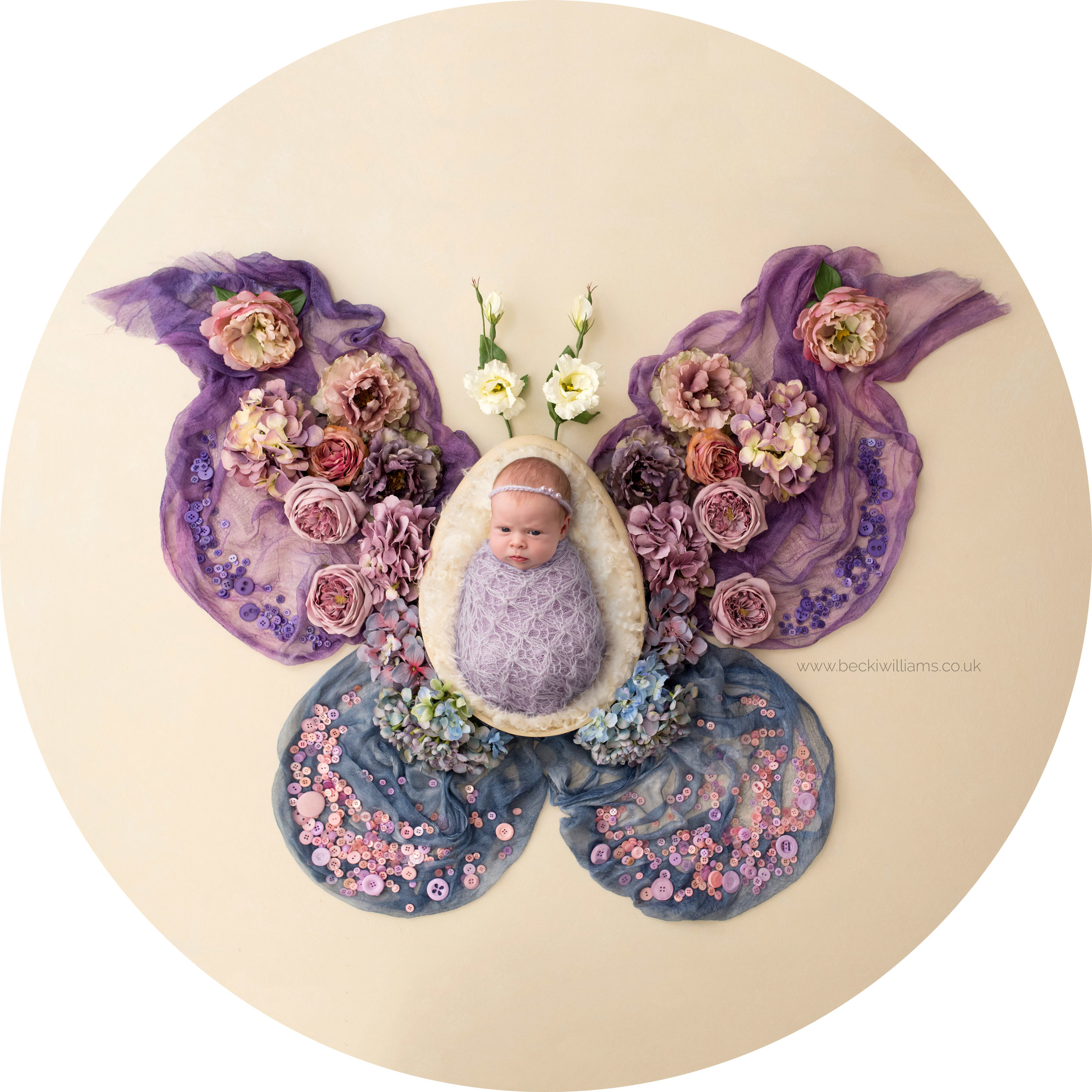 wrapped newborn girl laying on a butterfly shape made of flowers and blankets