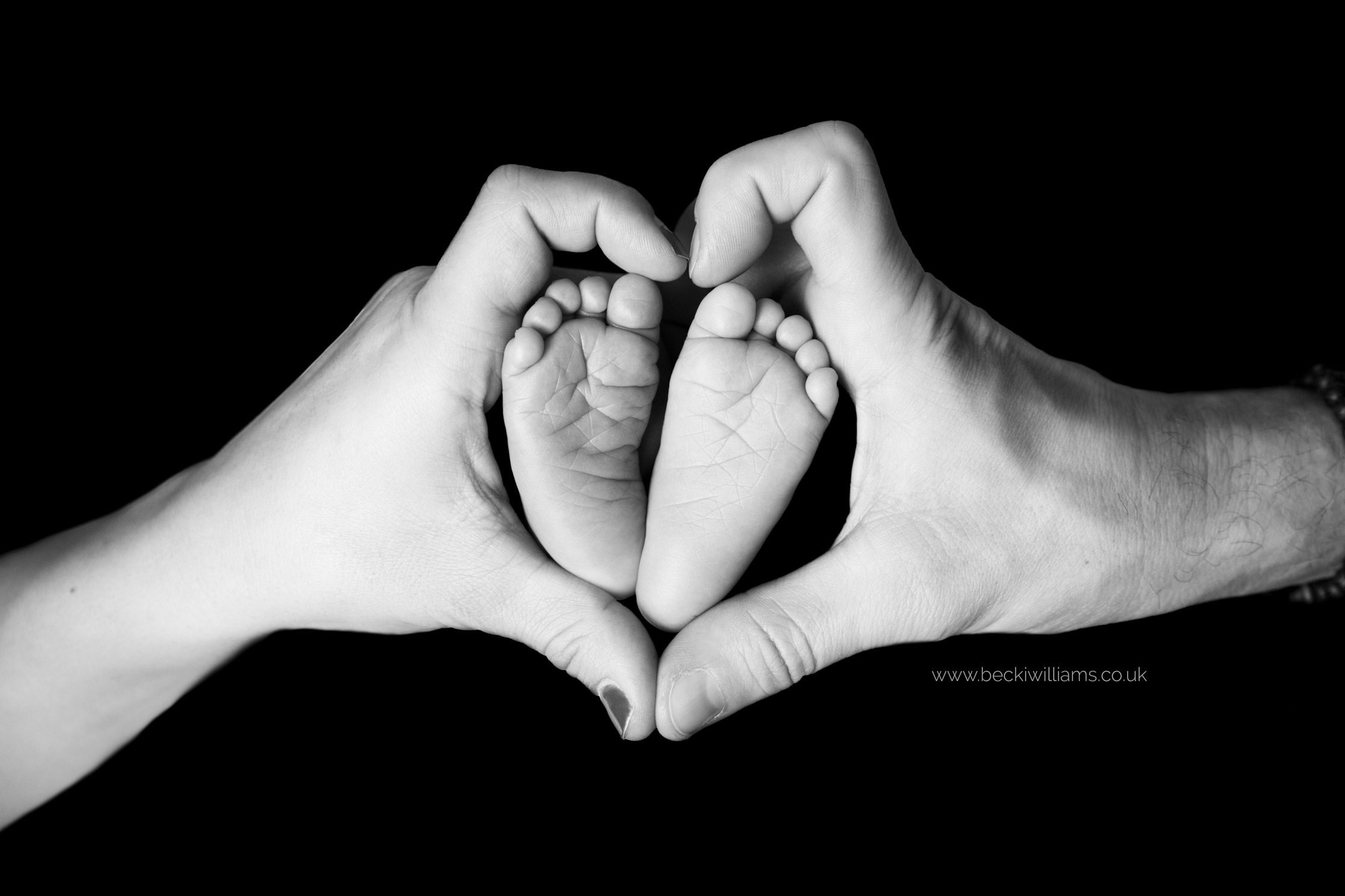 newborn feet inside parents hands making a heart shape in black and white