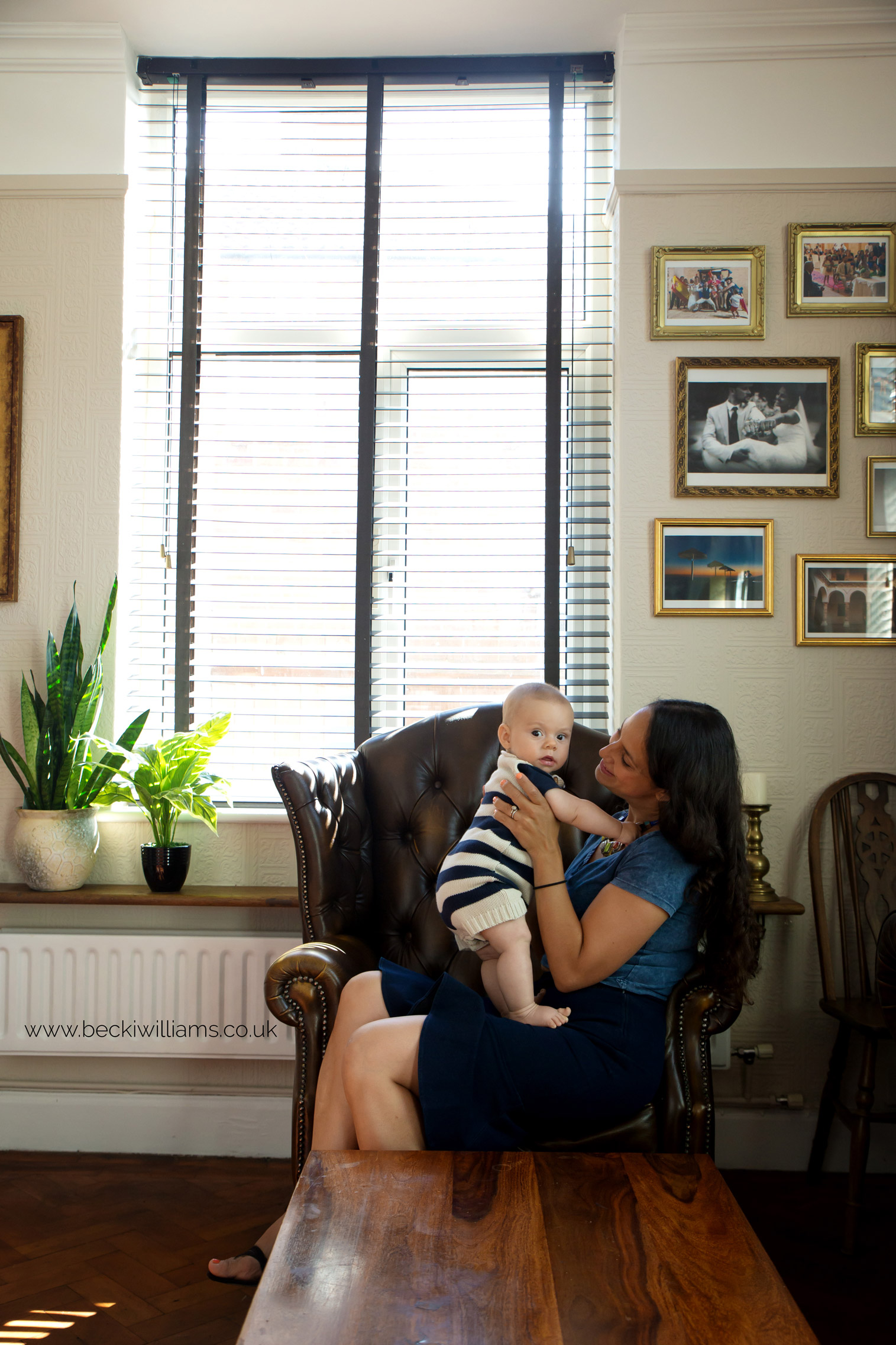 6 month old boy sitting on his mums lap in living room at home for photo shoot