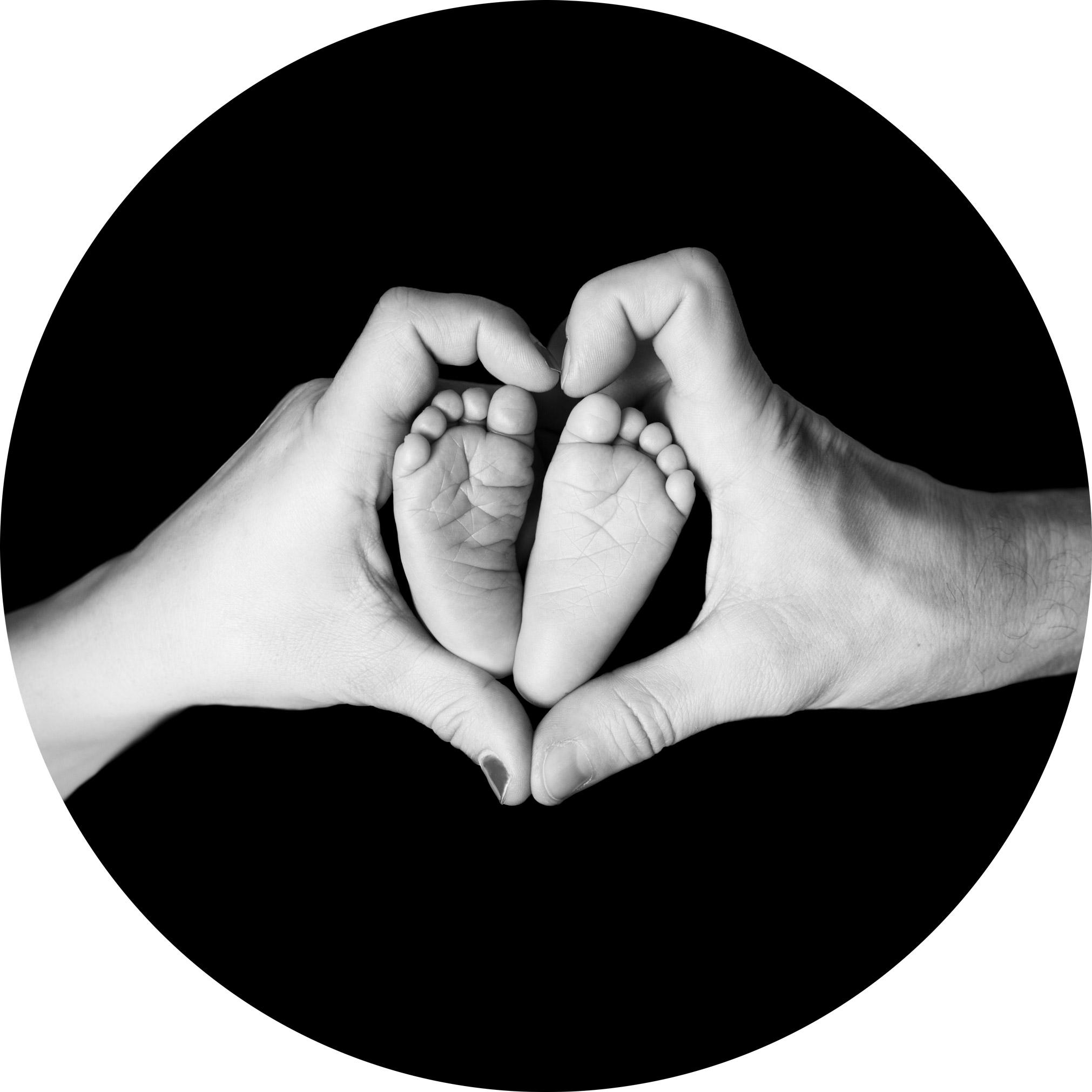 newborn feet in love heart made up of parents hands
