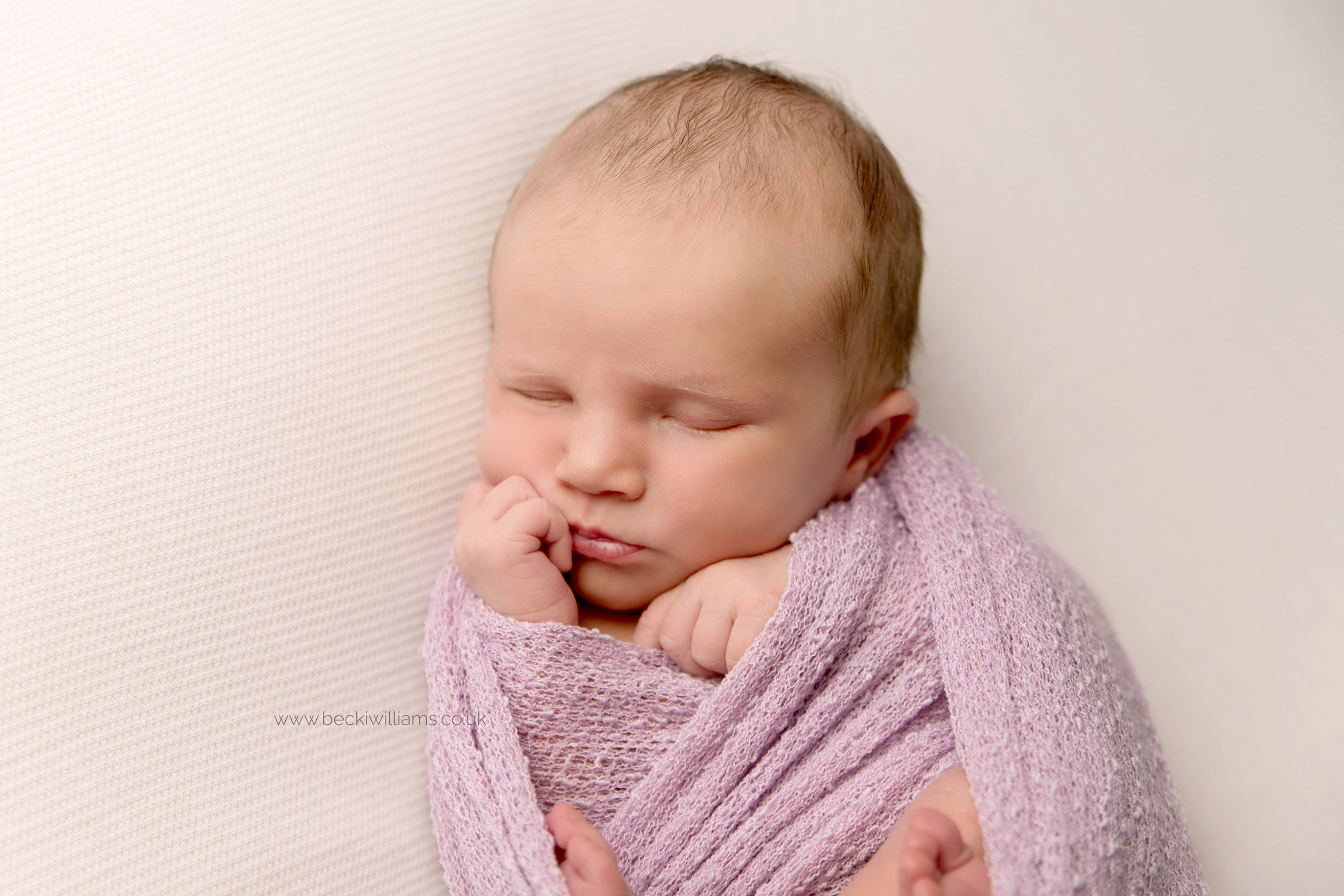 newborn baby girl, asleep, wrapped in a pink wrap for her newborn photo shoot in hemel hempstead