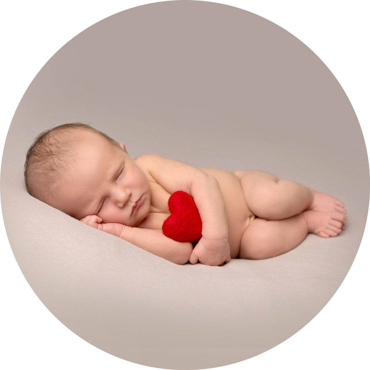 newborn baby girl laying asleep on her side holding a red heart for her newborn photo shoot in Hemel hempstead