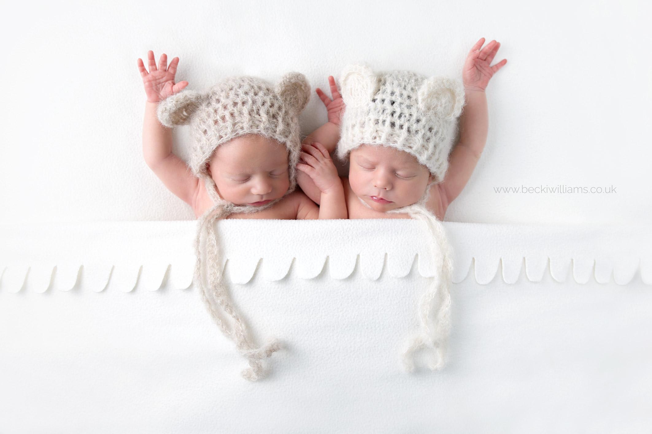 newborn twins wearing bear hats under w white blanket with their arms above their heads at their newborn photo shoot in Hemel hempstead