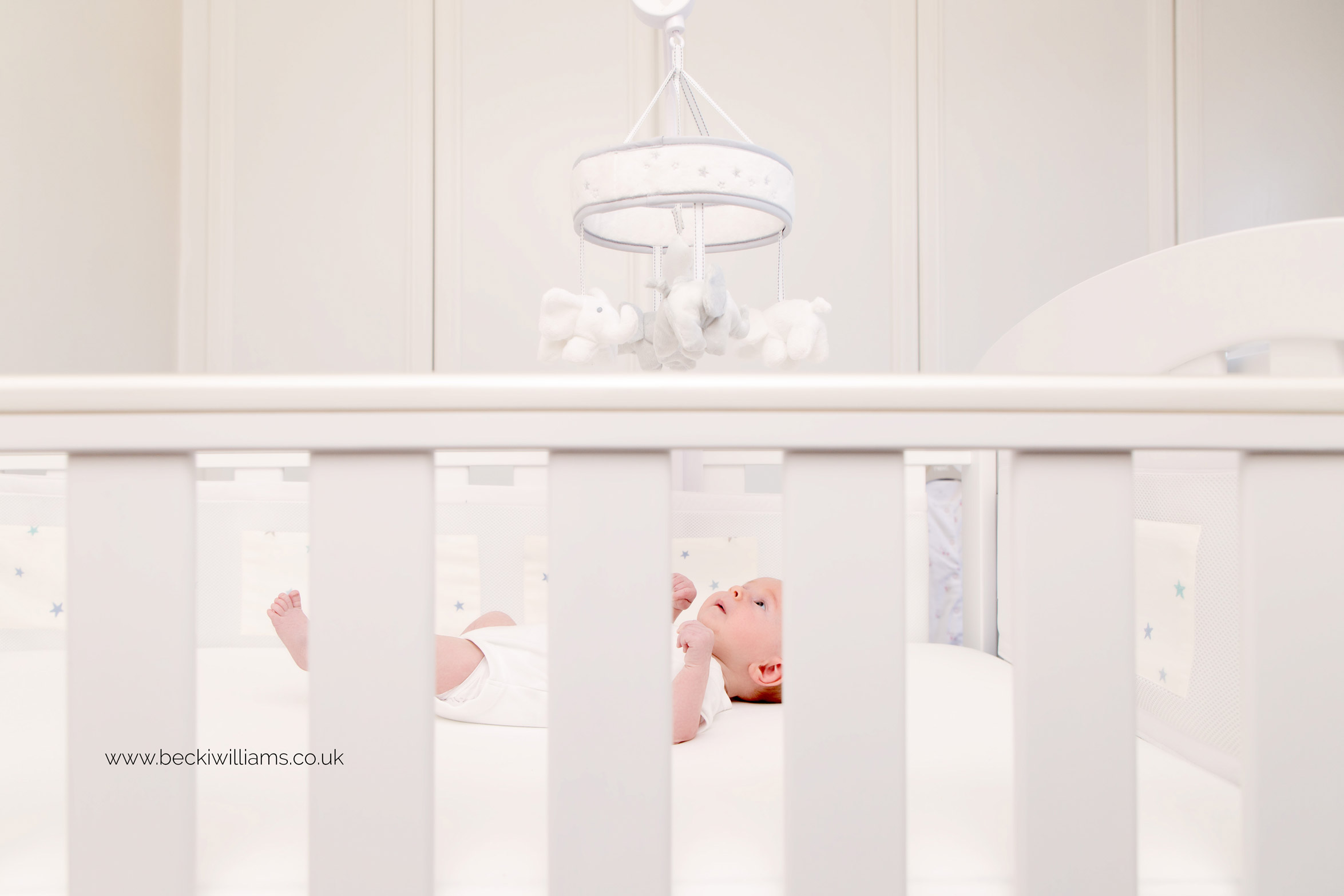 newborn baby girl laying in her white cot for her lifestyle newborn photo shoot in st albans