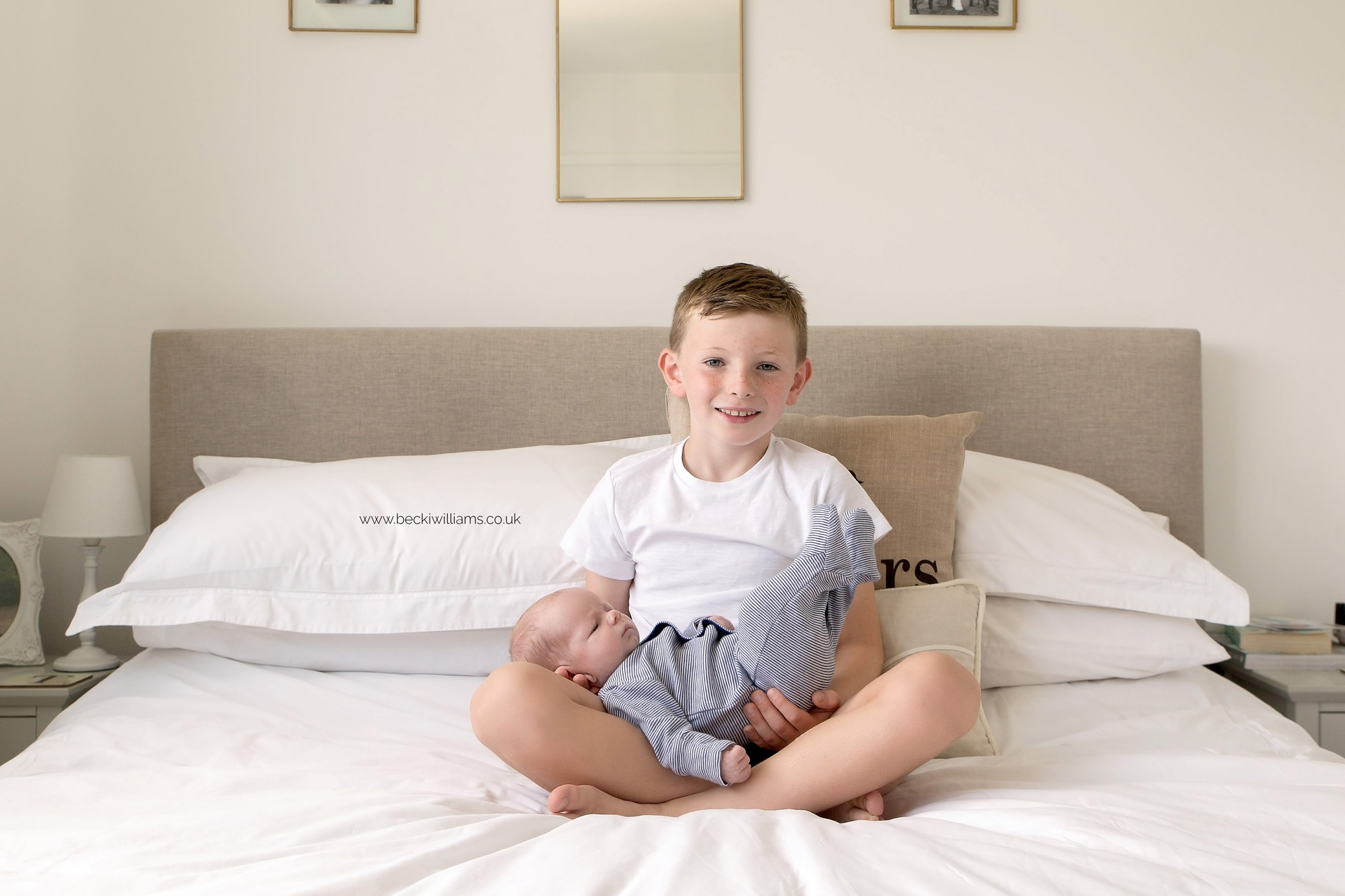 Big brother holding his newborn baby brother at their lifestyle newborn photo shoot in Hertfordshire