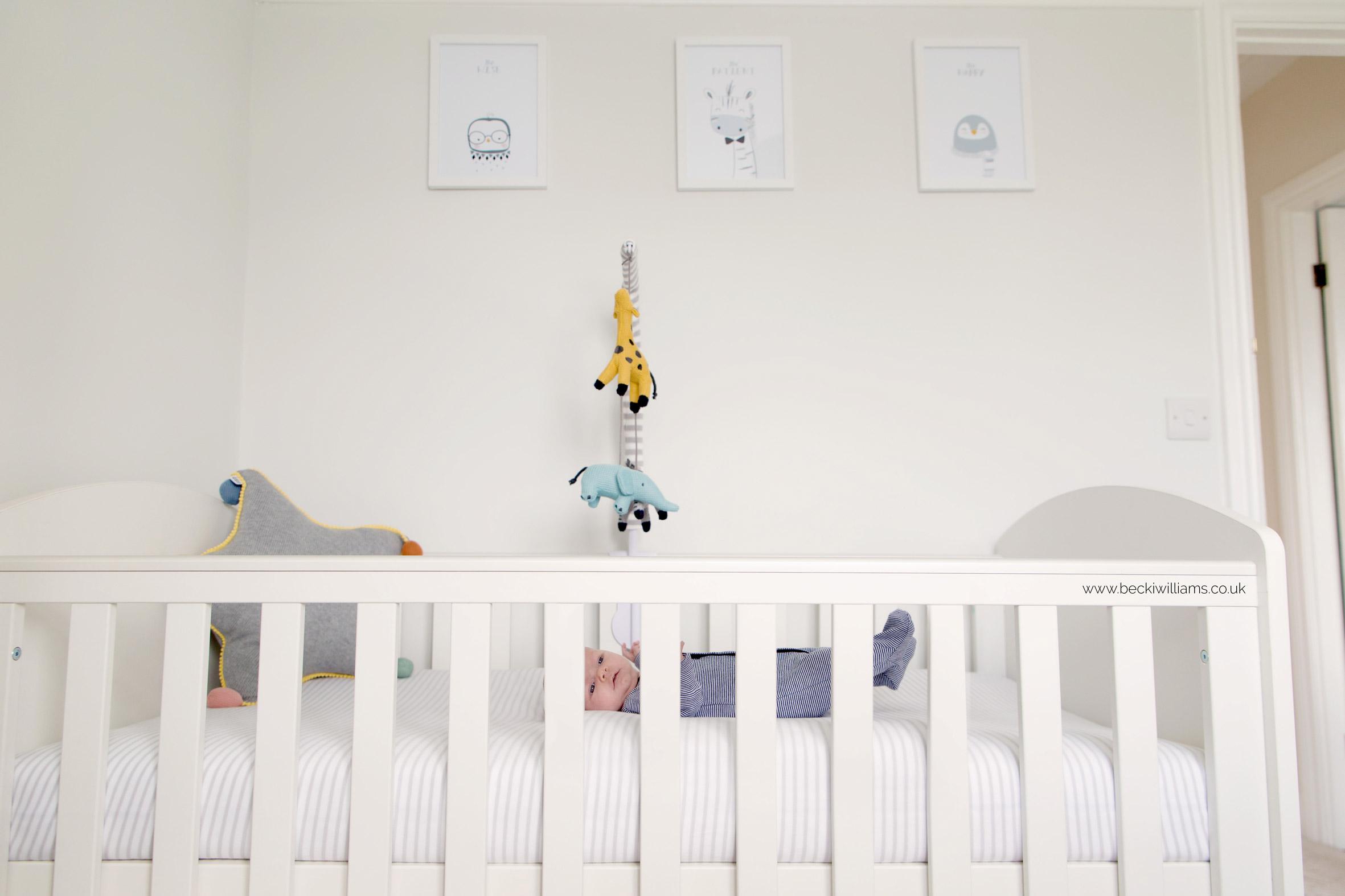 Newborn baby boy laying in his cot at his newborn photo shoot in Hertfordshire