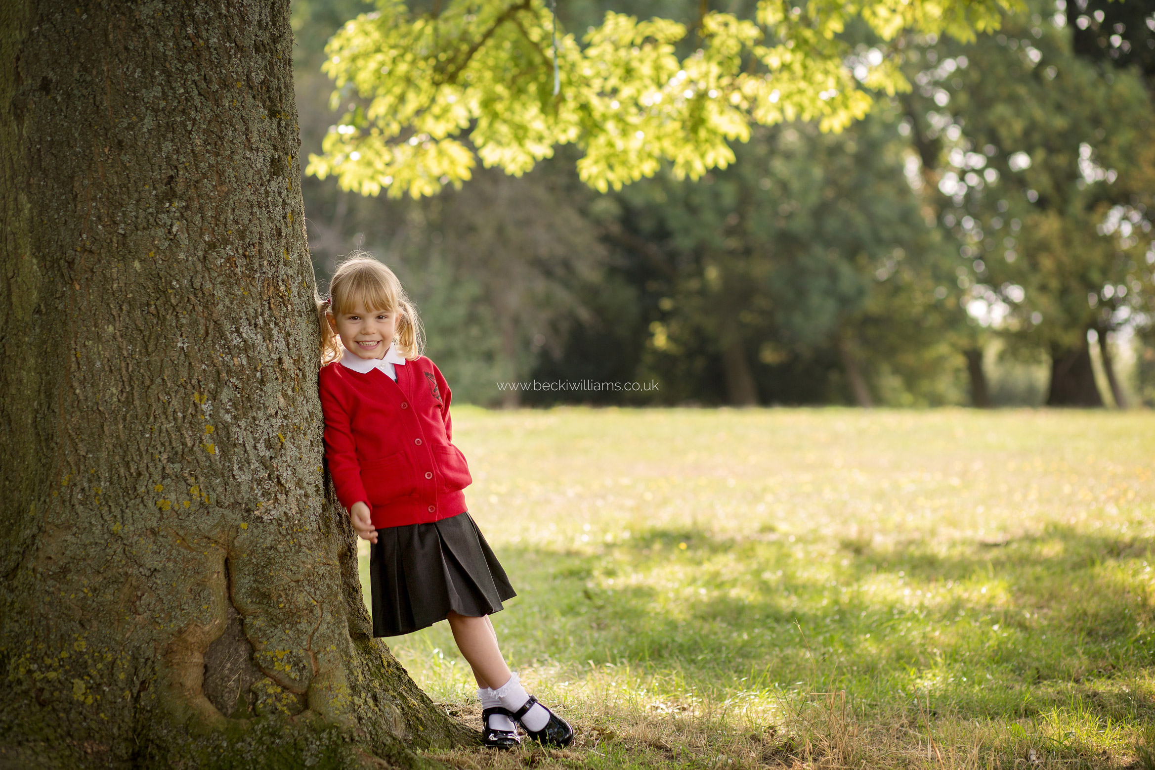 School girl standing under a tree for a Back To School photo shoot in Hertfordshire