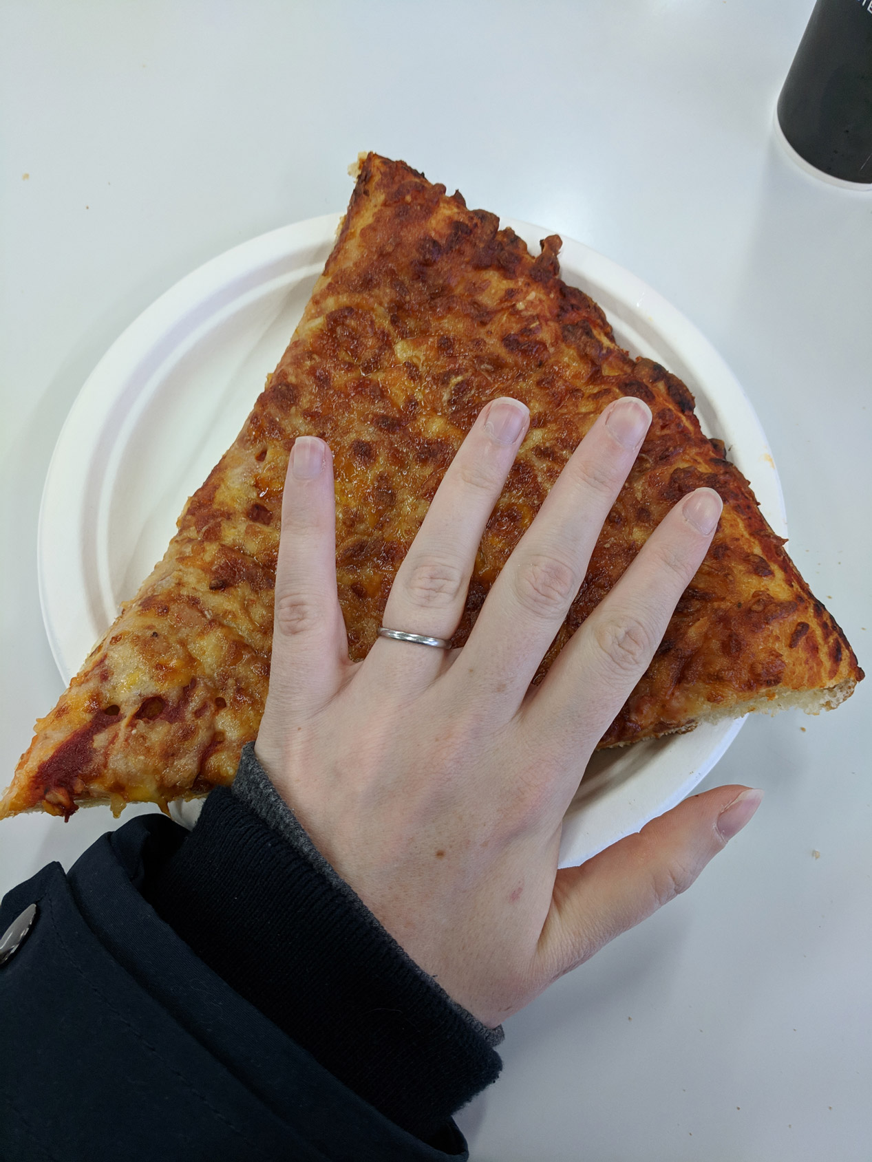 giant slice of pizza from costco in watford with hand hovering over it for scale