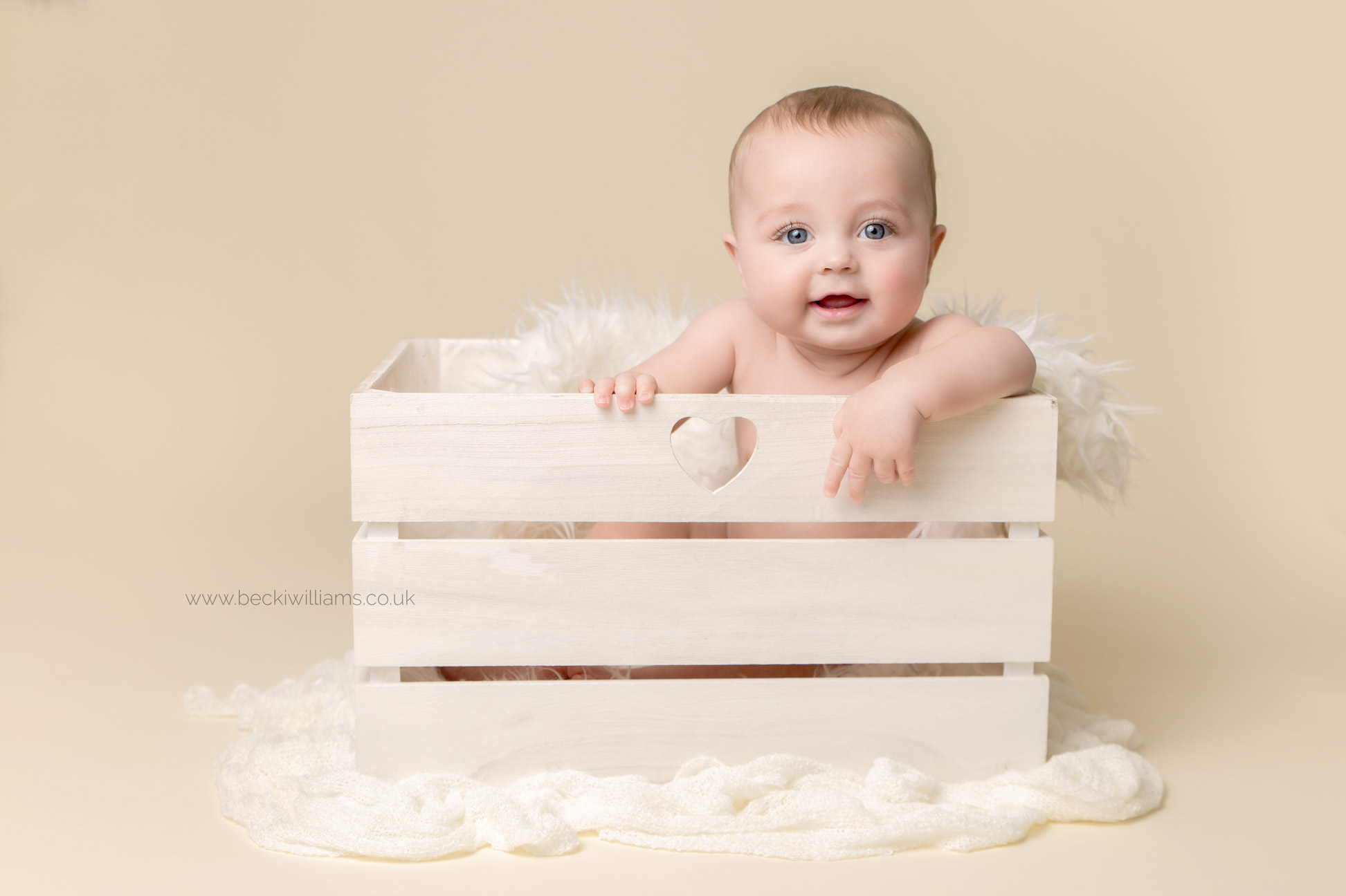 cute baby photo of a little boy sitting in a white crate, smiling at his professional photo shoot