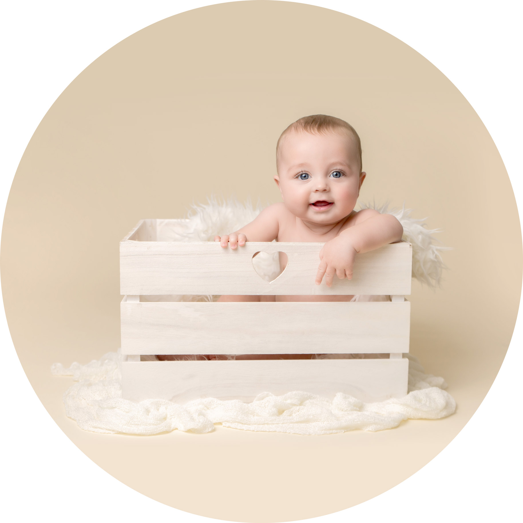 6 month old baby boy sitting in a white crate, smiling.