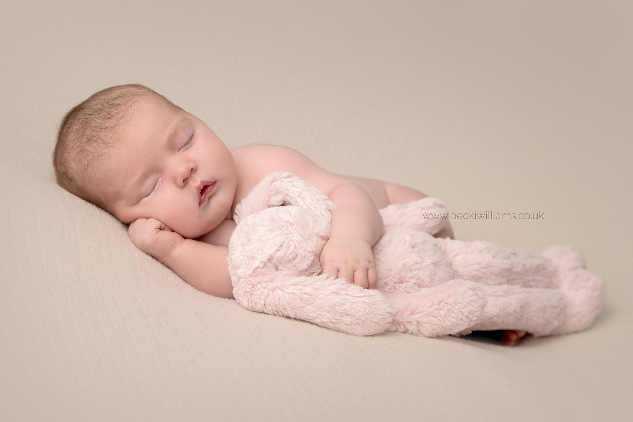 Newborn baby girl lays asleep on her side cuddling a pink bunny for her newborn girl portraits in Hemel Hempstead