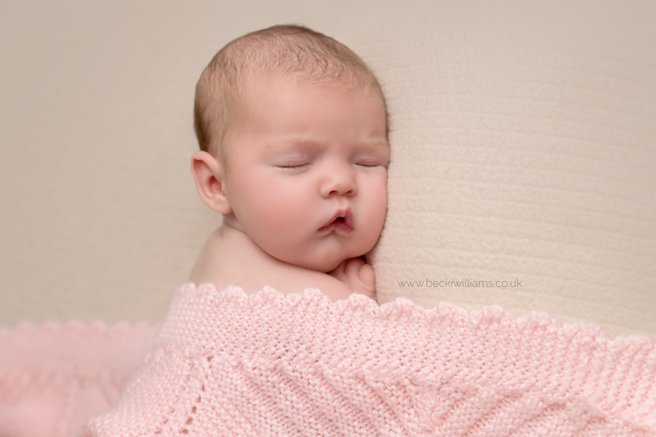 Close up photo of a newborn baby girl sleeping, covered in a pink blanket at her newborn photo shoot in Hemel hempstead