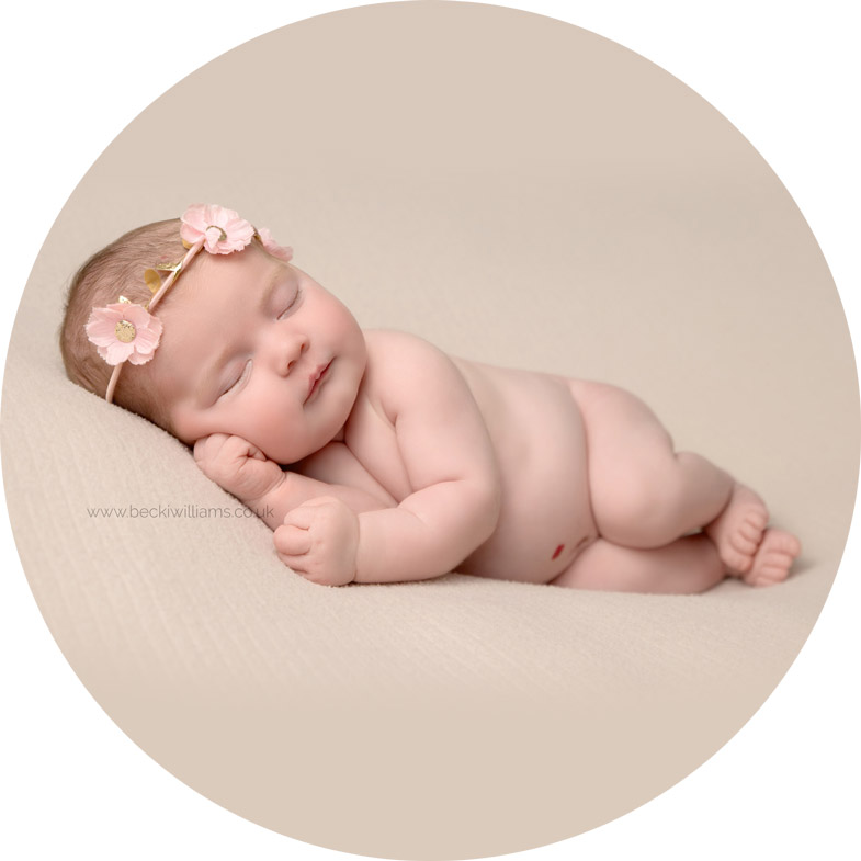 newborn girl laying on her side wearing a pink flower headband for her newborn photo shoot with Becki williams photography