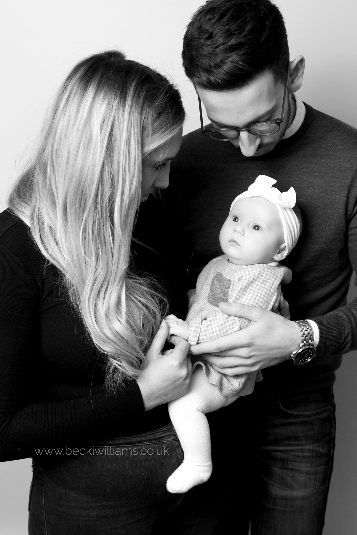 new parents hold their new 2 month old baby girl