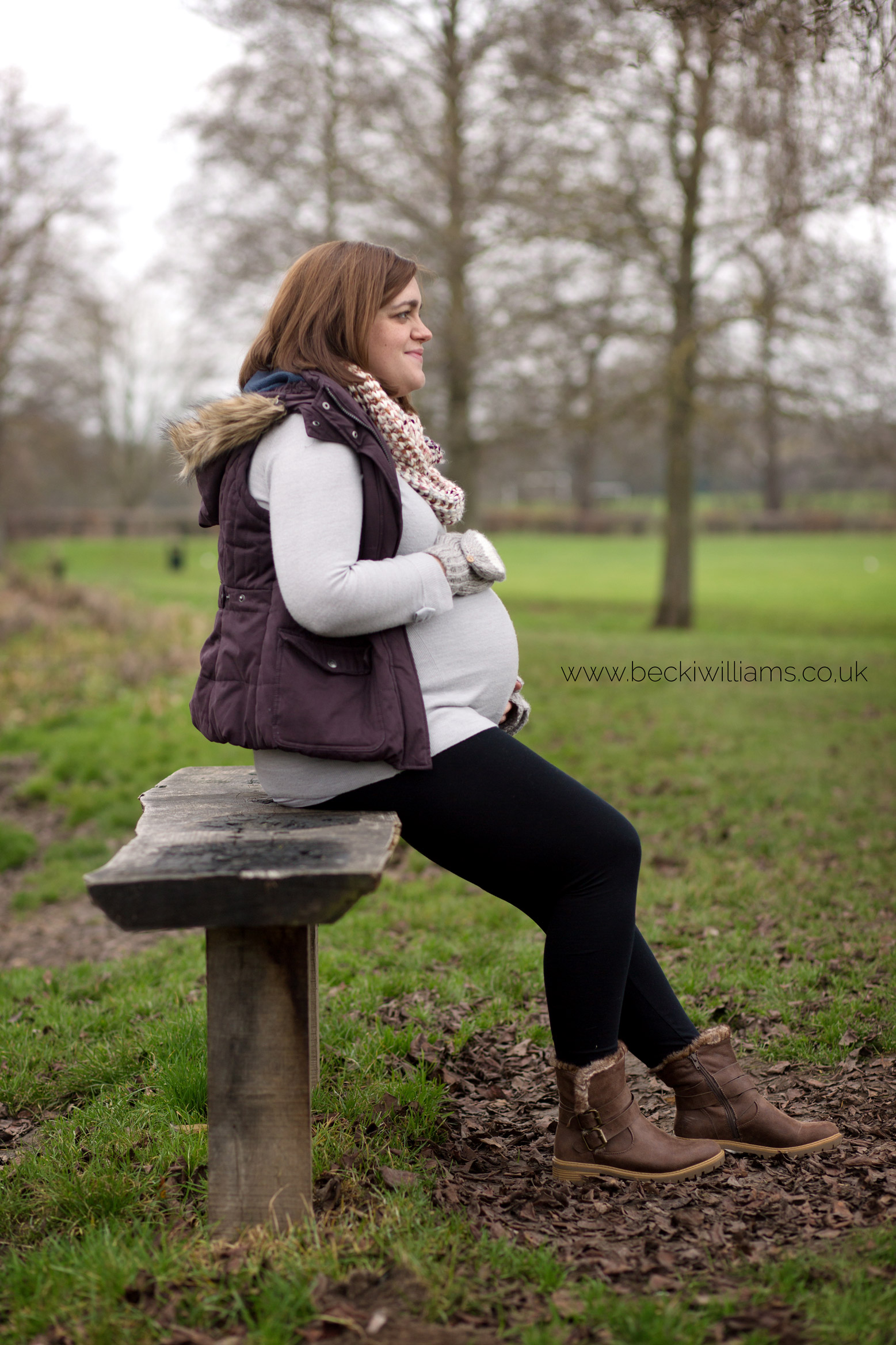 maternity photo shoot in gadebridge park - pregnant lady sits side on on a park bench, holding her tummy
