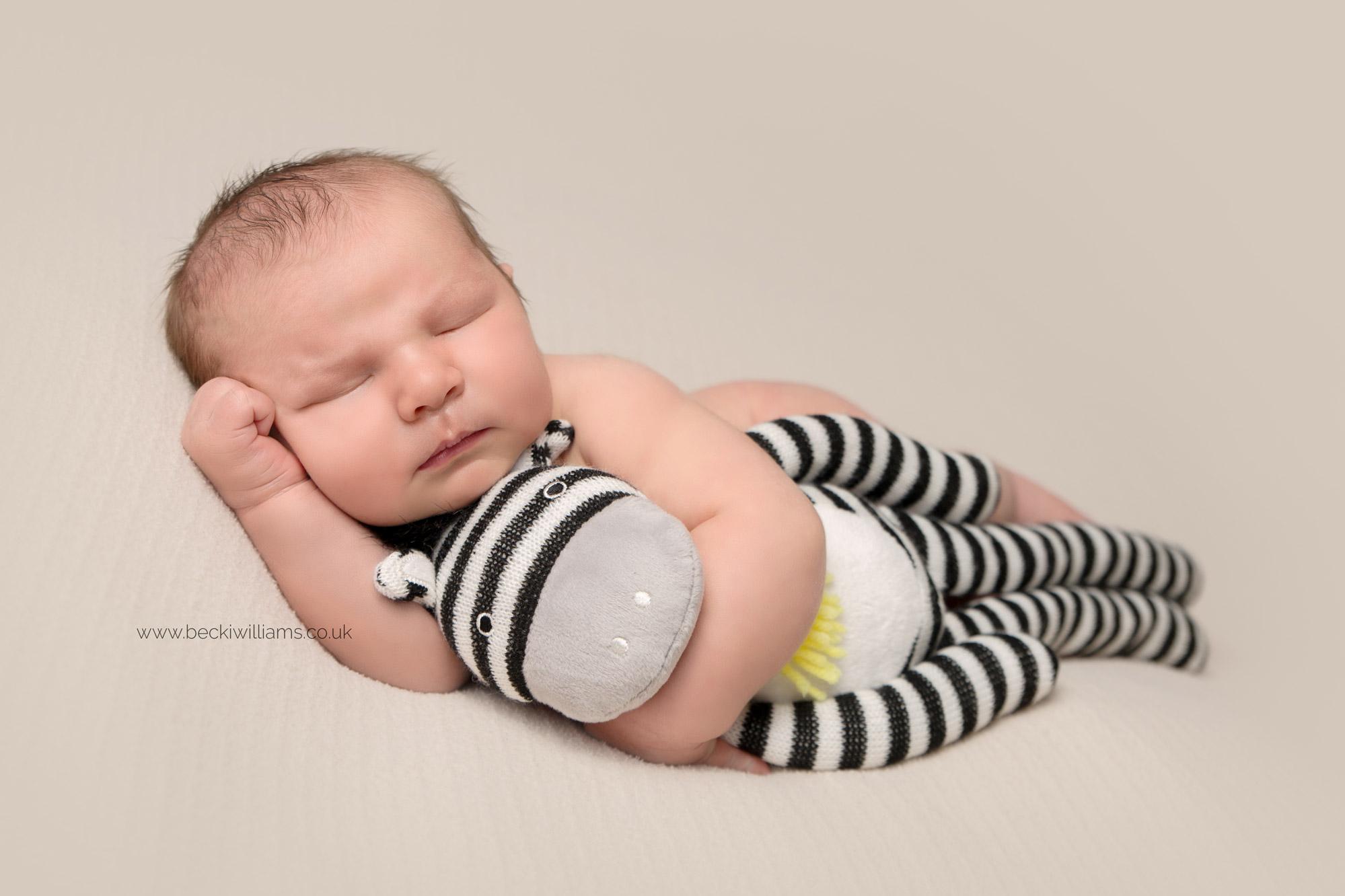 newborn boy laying asleep on his side hugging a sock monkey at his newborn photo shoot in hemel hempstead