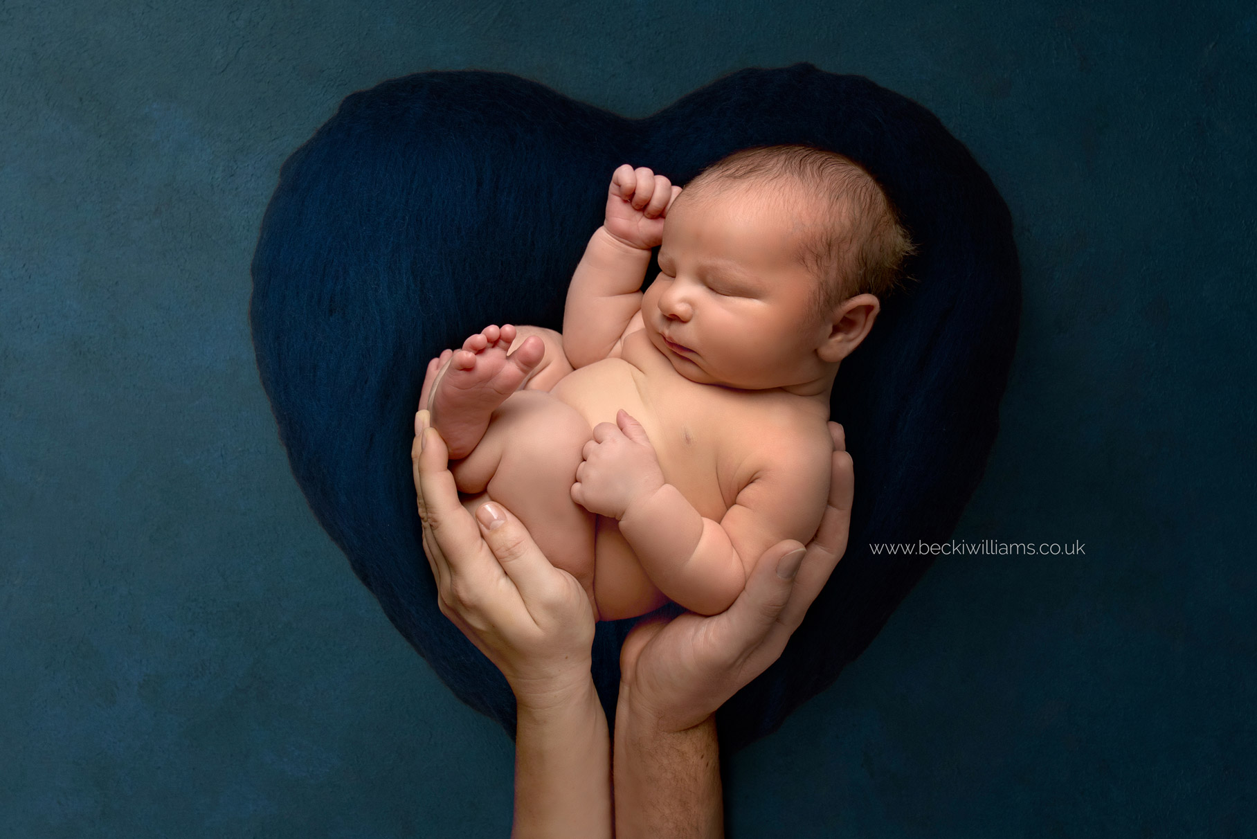 composite image using a luisa dunn backdrop of a baby laying curled up in his parent's hands on a blue heart backdrop