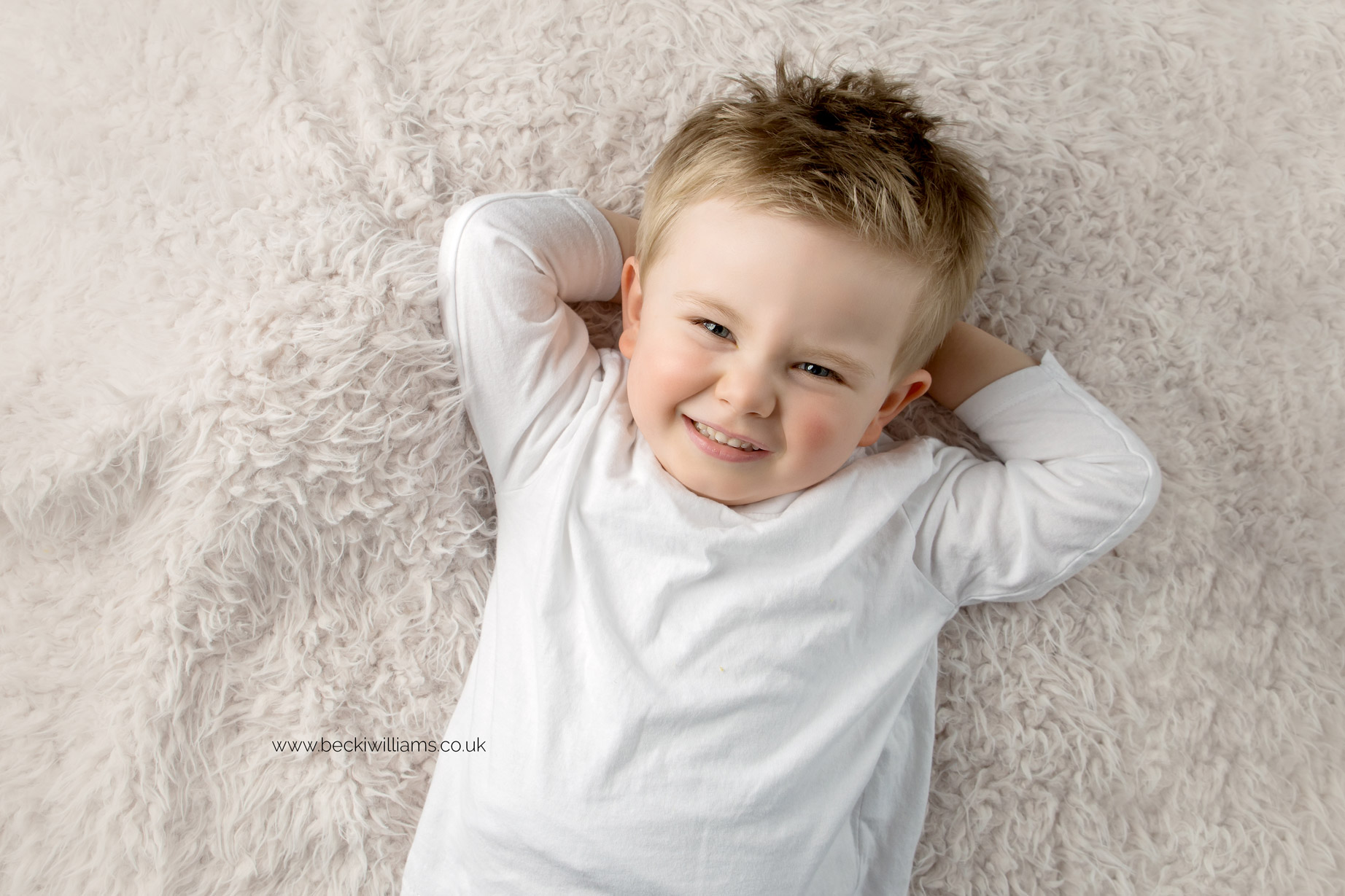 3 year old boy laying on his back with his hands behind his head at his photo shoot in hemel hempstead