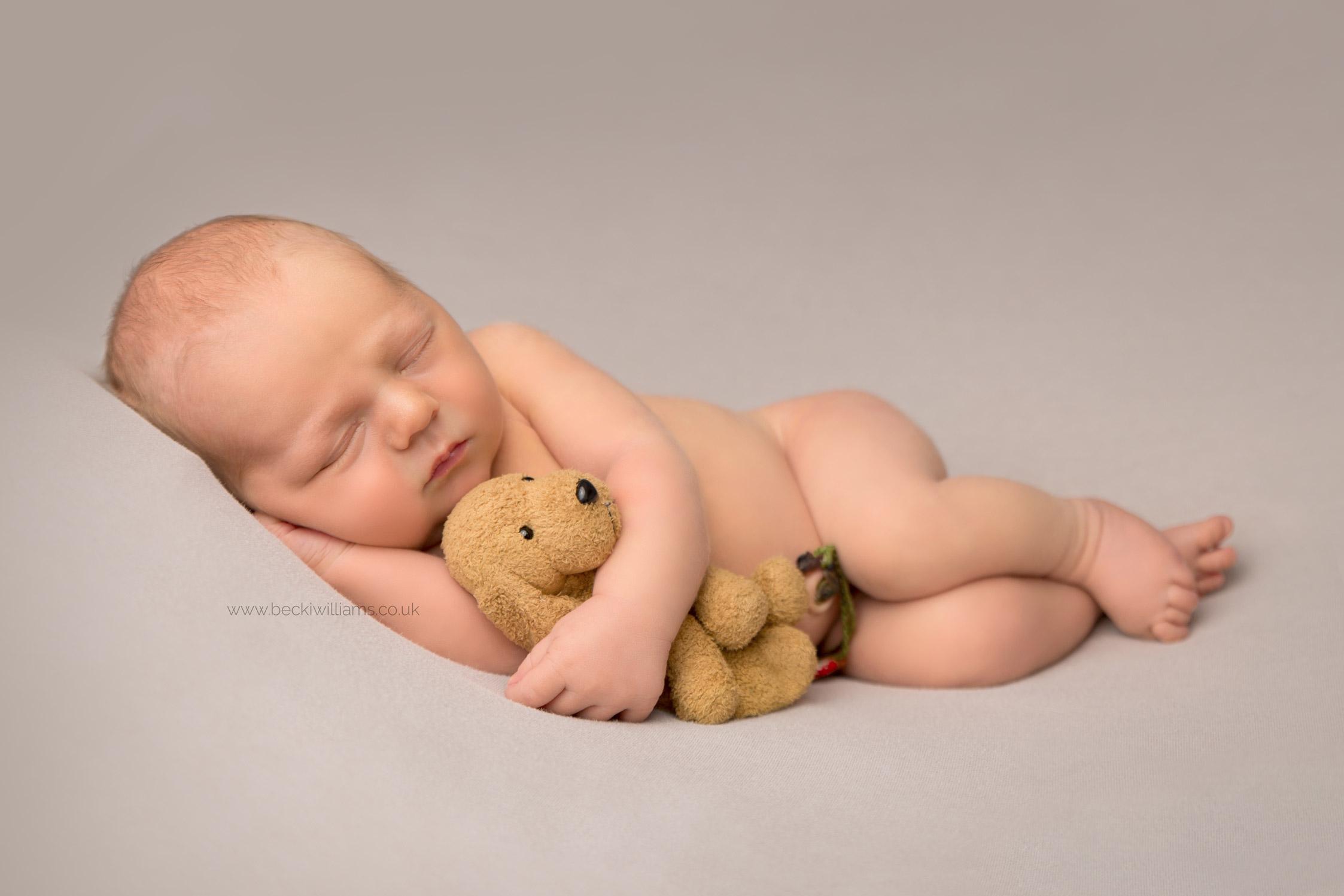 newborn baby boy laying asleep on his side at his newborn baby photo shoot in hemel hempstead