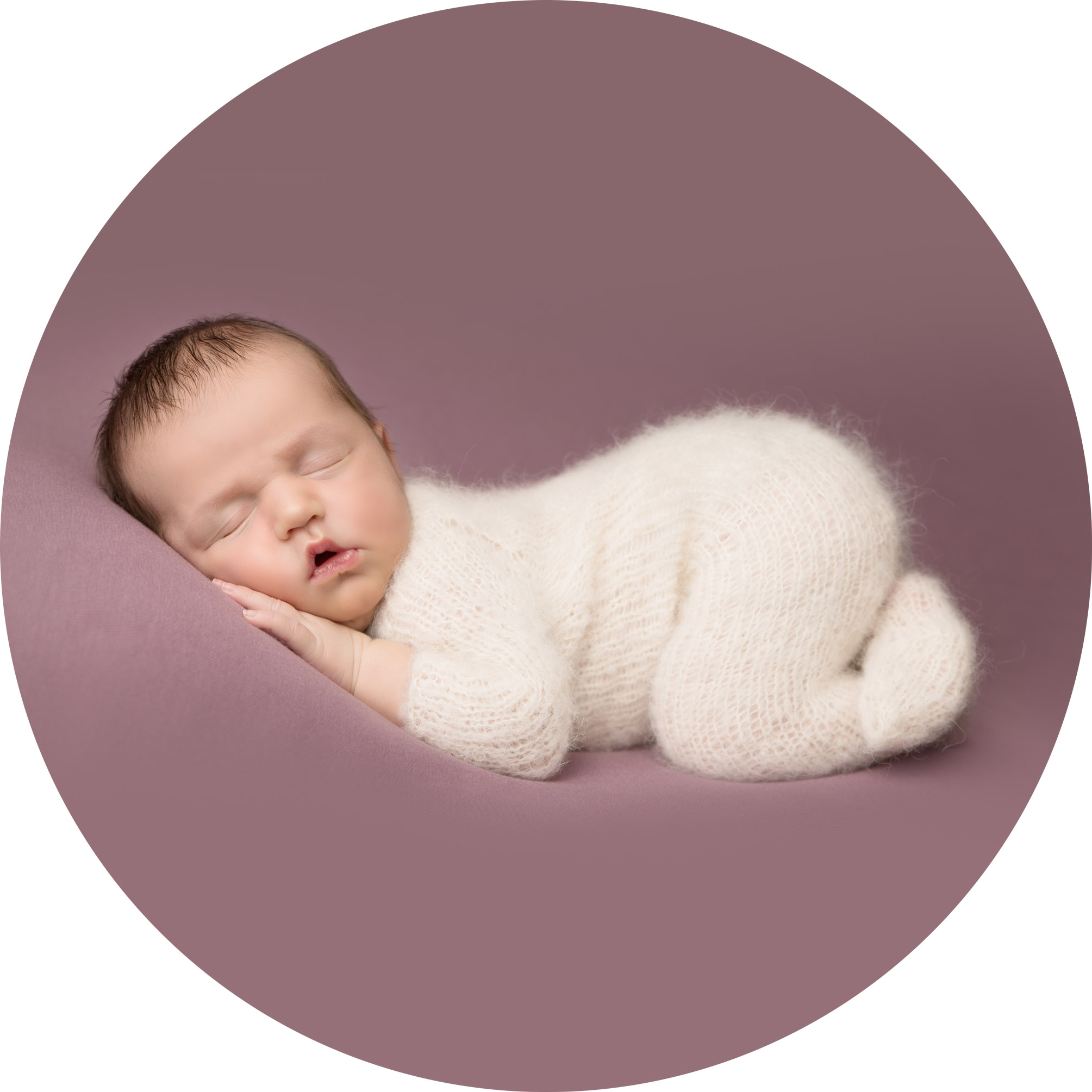 newborn baby girl laying on a mauve blanket asleep on her tummy wearing a white fluffy onesie.