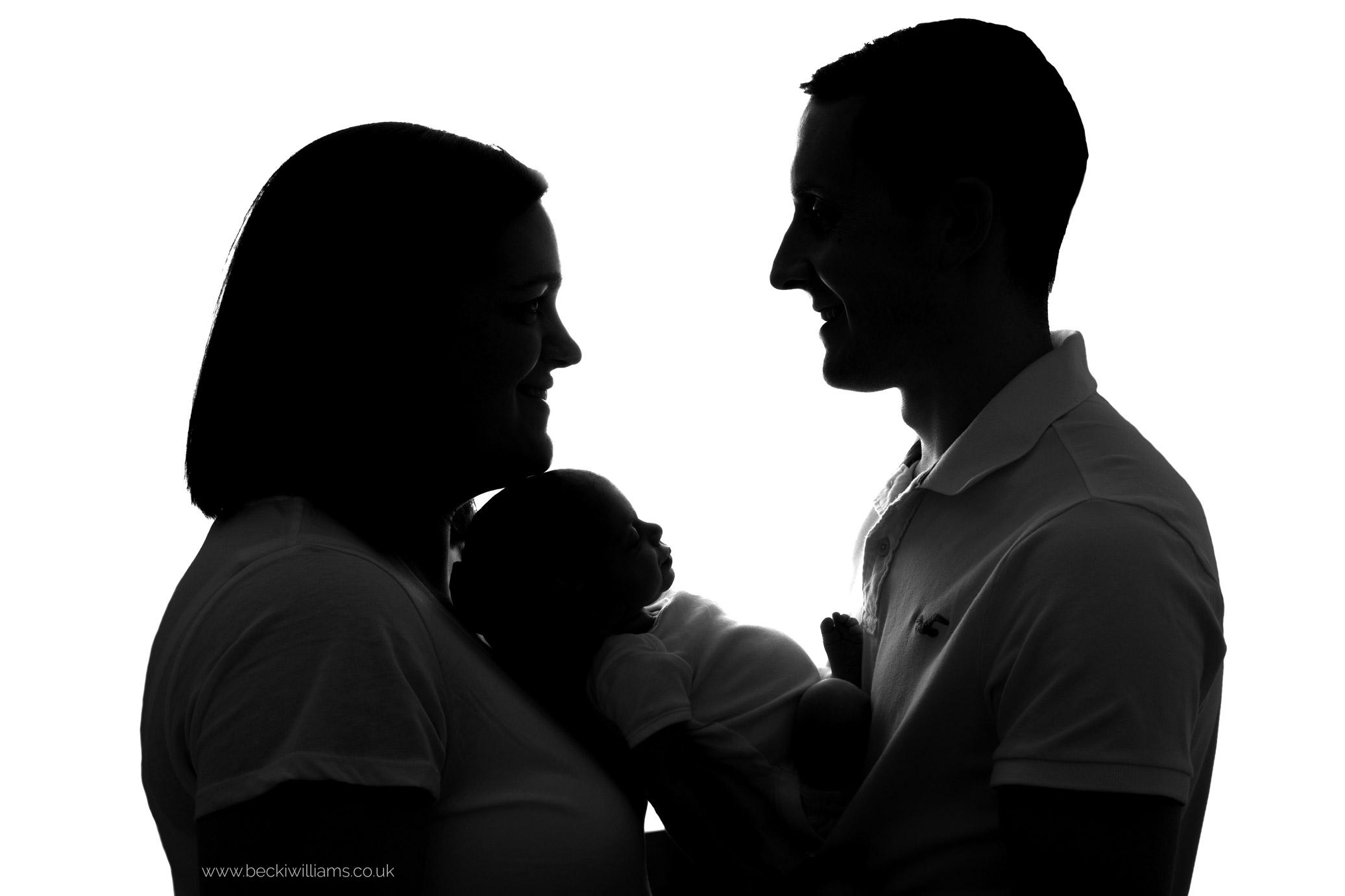 Black and white silhouette of parents holding their newborn baby girl at their newborn photo shoot in hemel hempstead