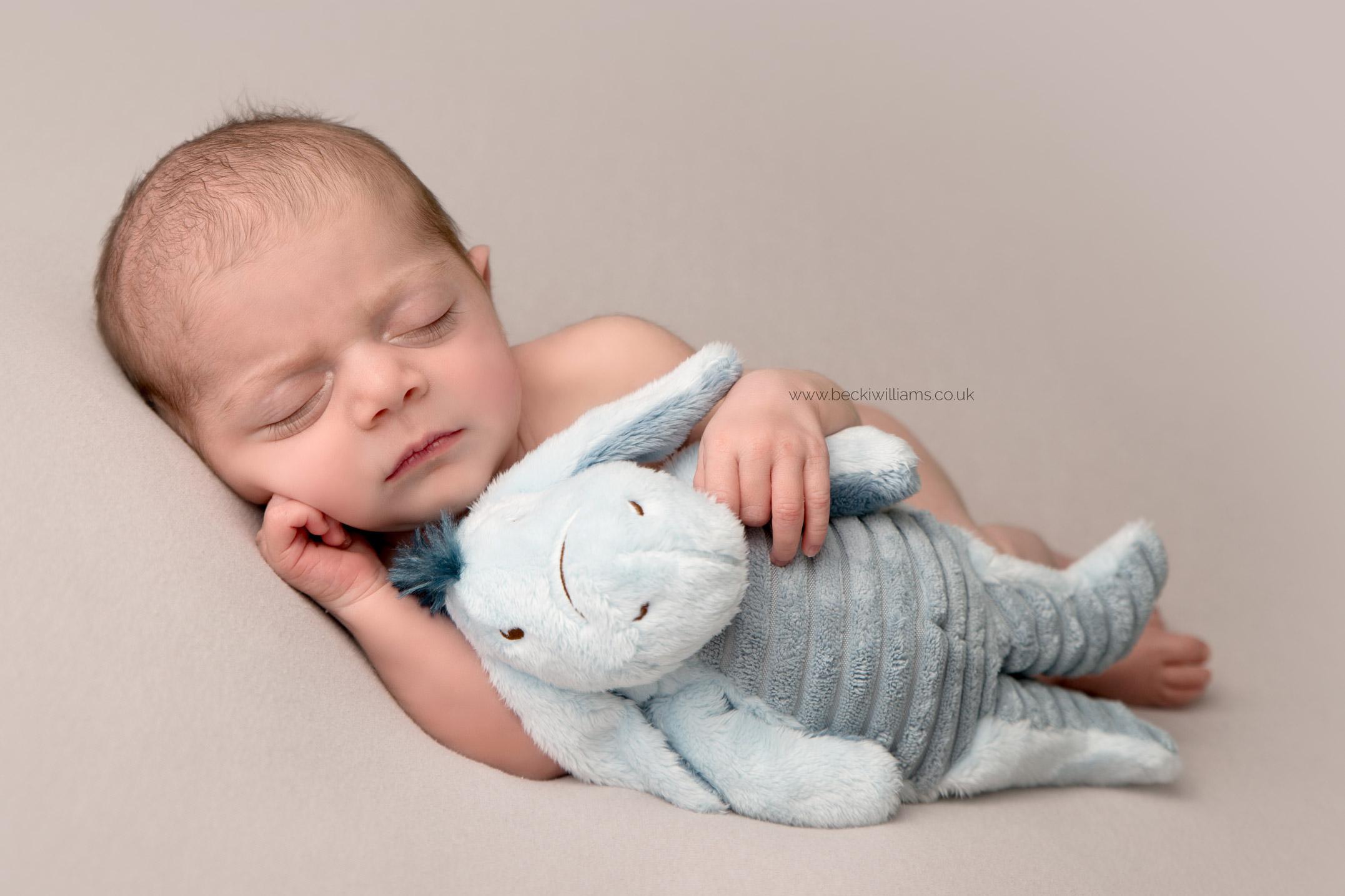 a baby girl asleep on her side cuddling a toy eeyore at her newborn photo shoot in hemel hempstead