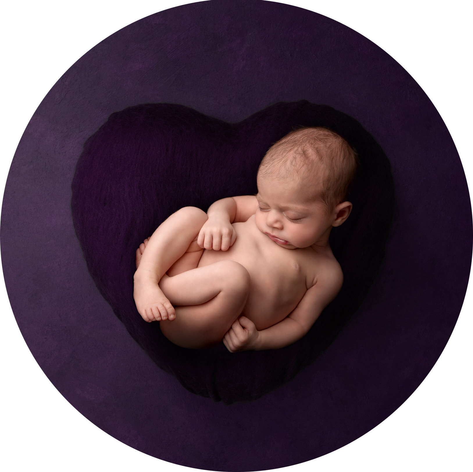 newborn baby girl lays asleep curled up on a giant purple heart shaped cushion at her newborn photo shoot in hemel hempstead