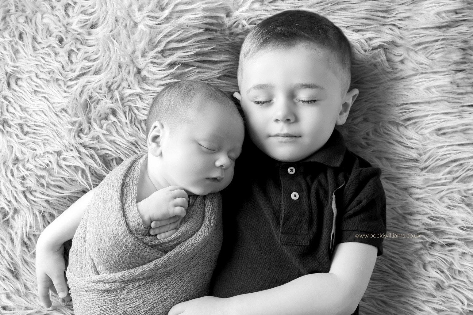 newborn baby boy cuddles up to his big brother at his newborn photo shoot i nhemel hempstead