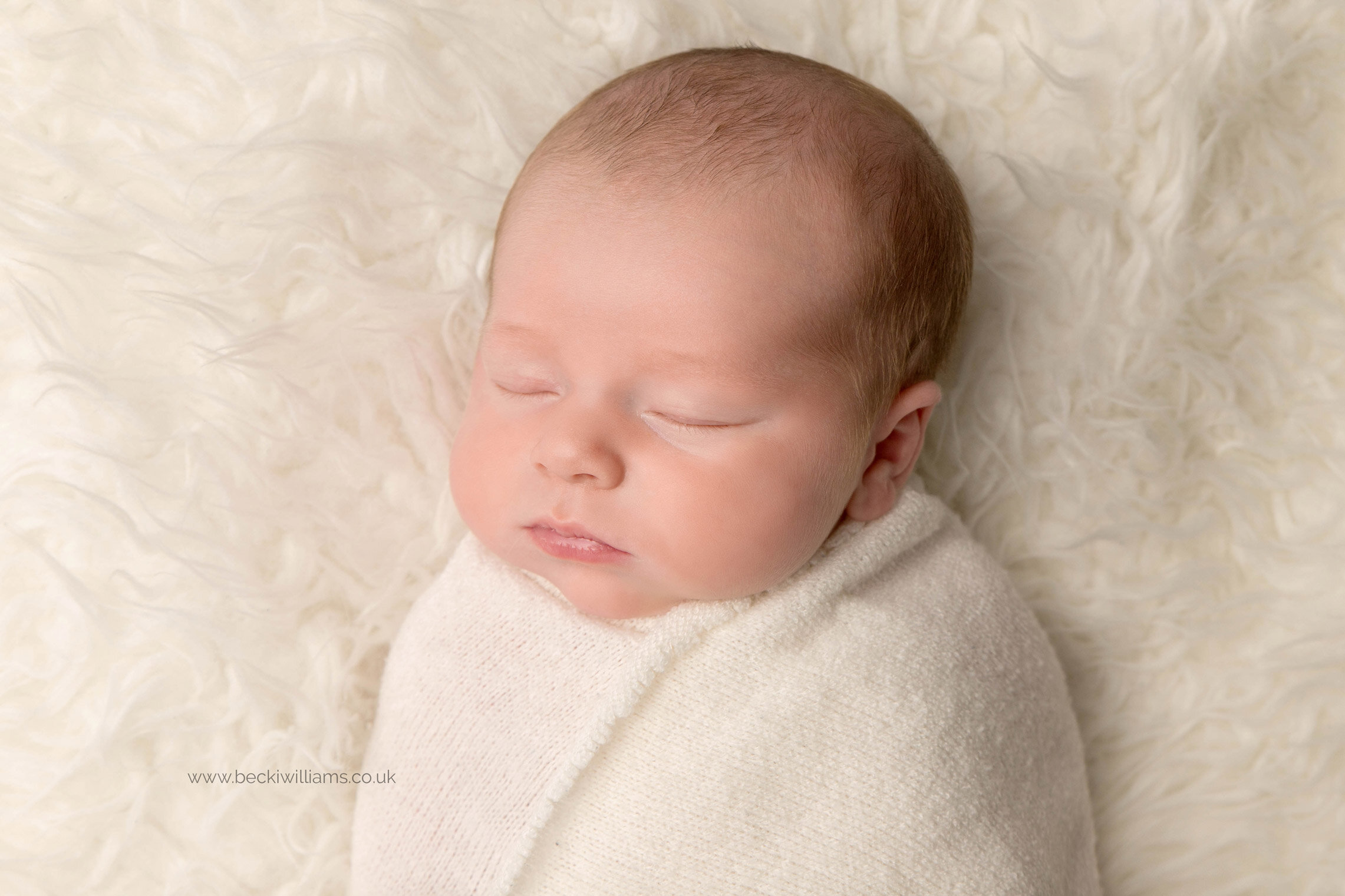 newborn baby boy wrapped in a white wrap, laying asleep on a white fluffy blanket for his newborn pictures in hemel hempstead