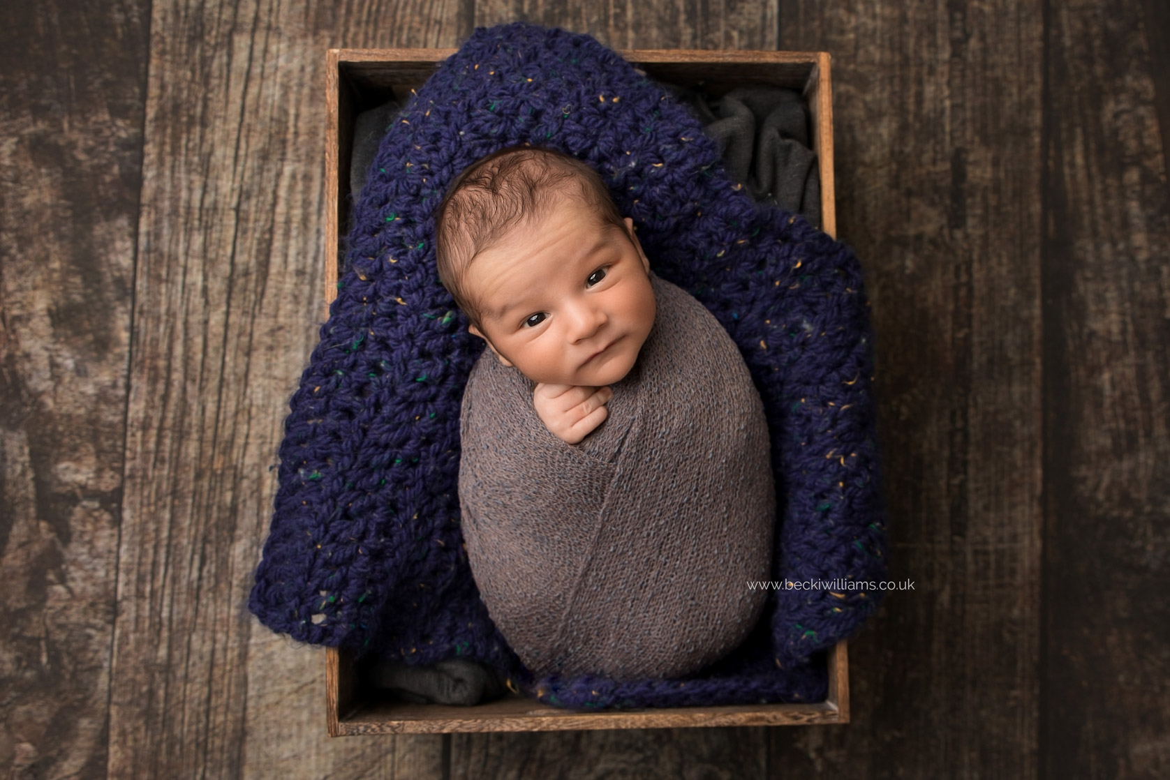 newborn boy laying on blue in a crate for his newborn photo shoot in hemel hempstead