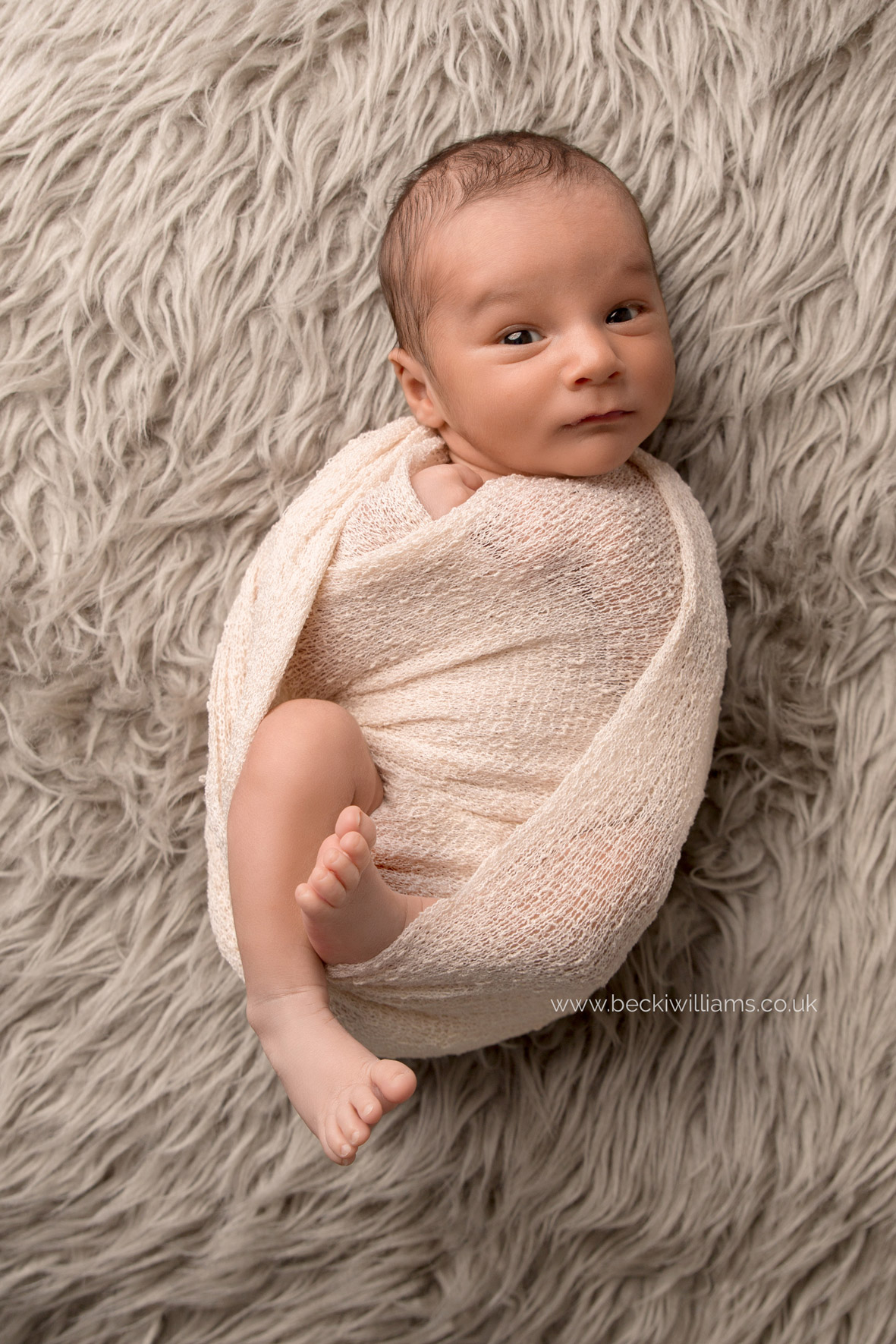 newborn baby boy wrapped in a cream wrap on a furry blanket for his newborn photo shoot in hemel hempstead