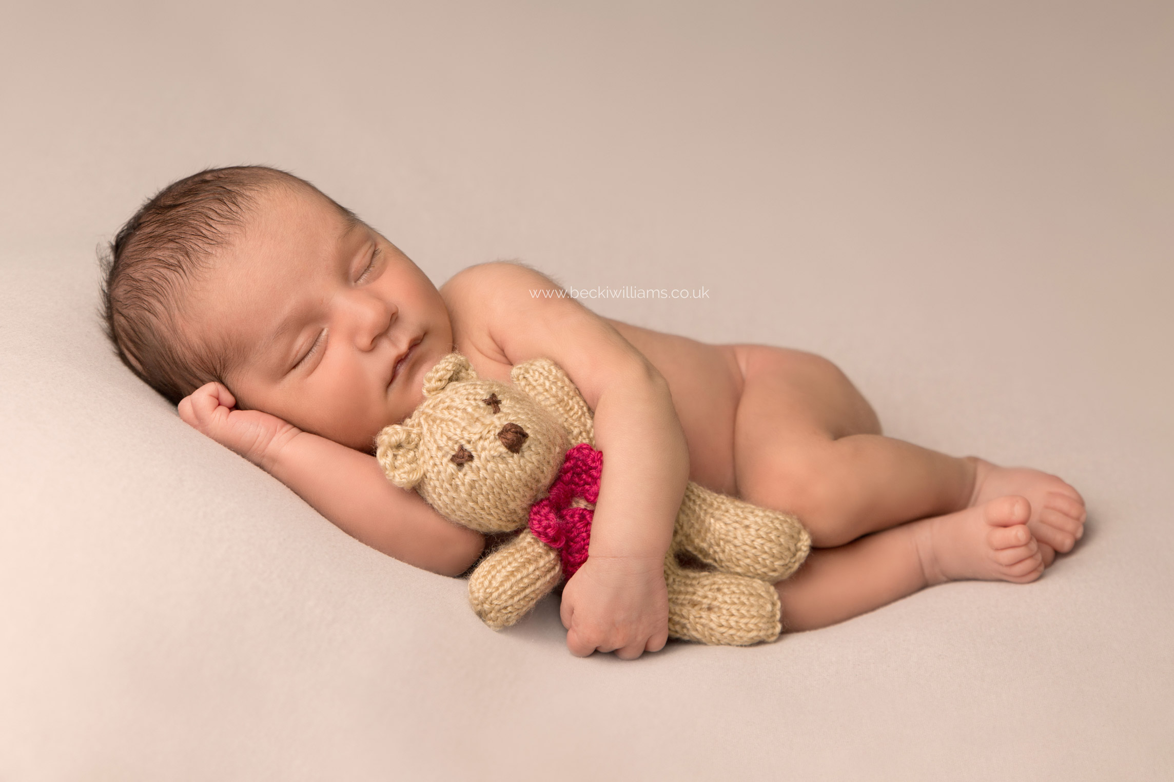 newborn baby boy asleep on his side cuddling a teddy bear for his newborn photo shoot in hemel hempstead