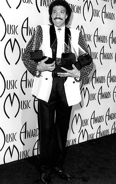 Lionel Richie in 1985  Lionel Richie, too, has his arms full at the 1985 AMAs.