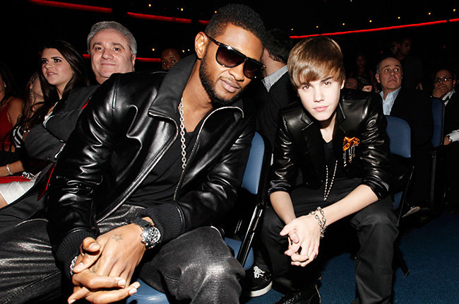 Usher and His Protege in 2010  Usher and Justin Bieber sat in the audience in matching black jackets at the 2010 AMAs.