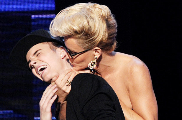 Jenny McCarthy's Big Kiss in 2012  Presenter Jenny McCarthy plants a playful kiss on winner Justin Bieber as he accepts the award for Favorite Pop/Rock Album at the 2012 AMAs.