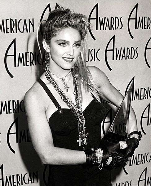 Madonna in 1985  Madonna cradles her award at the 1985 AMAs.