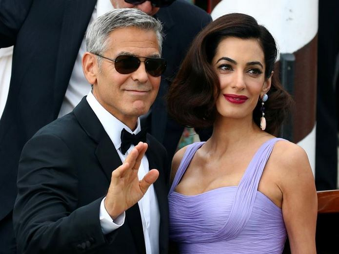 """Actor and director George Clooney waves next to his wife Amal as they leave the hotel before the red carpet for the movie """"Suburbicon"""". REUTERS/Alessandro Bianchi"""
