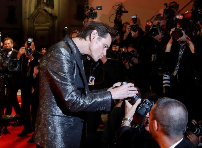 """Actor Jim Carrey jokes with photographers as he arrives during a red carpet event for the movie """"Jim & Andy: The Great Beyond"""". REUTERS/Alessandro Bianchi"""