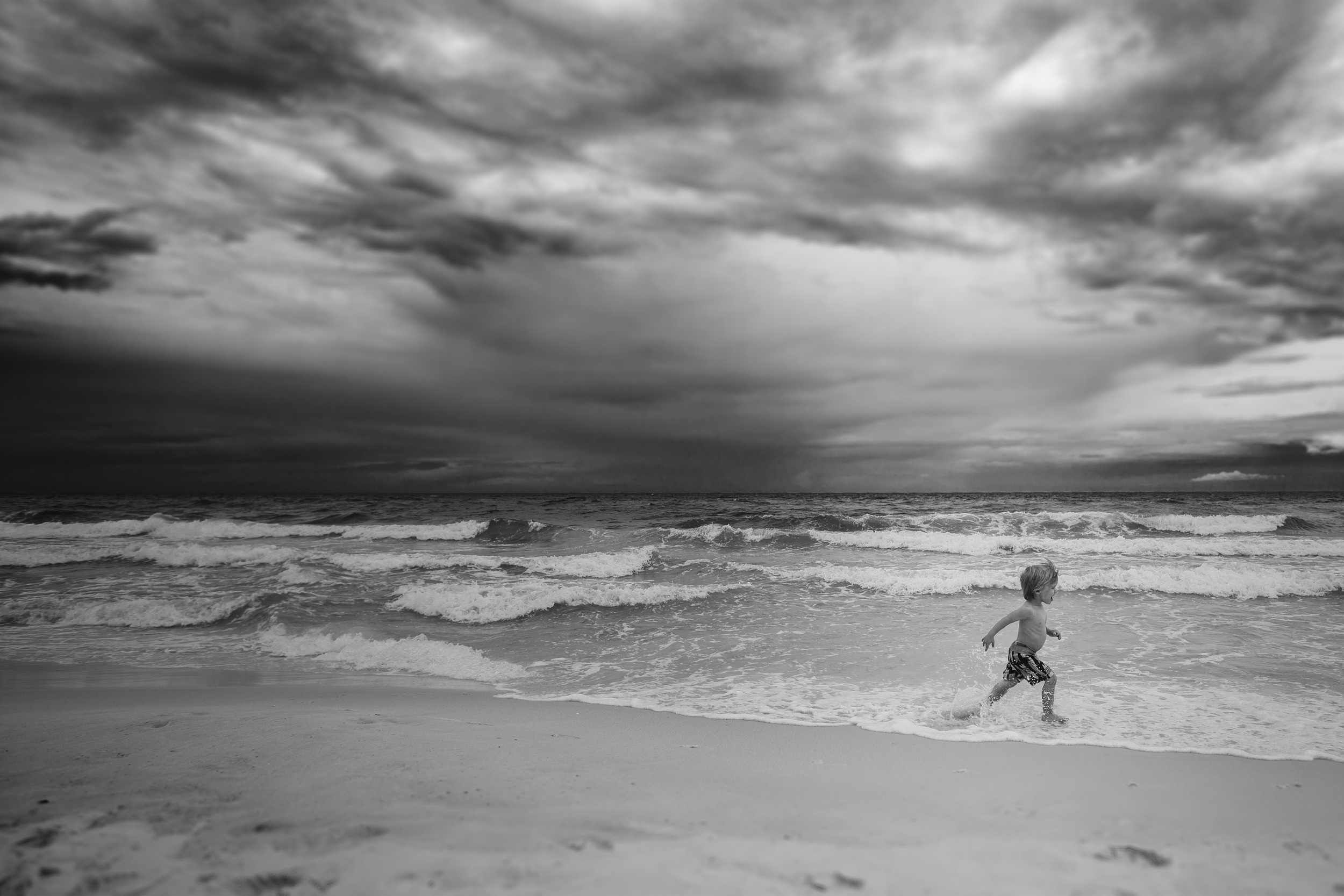 Child running on the beach by Rachel K Photo