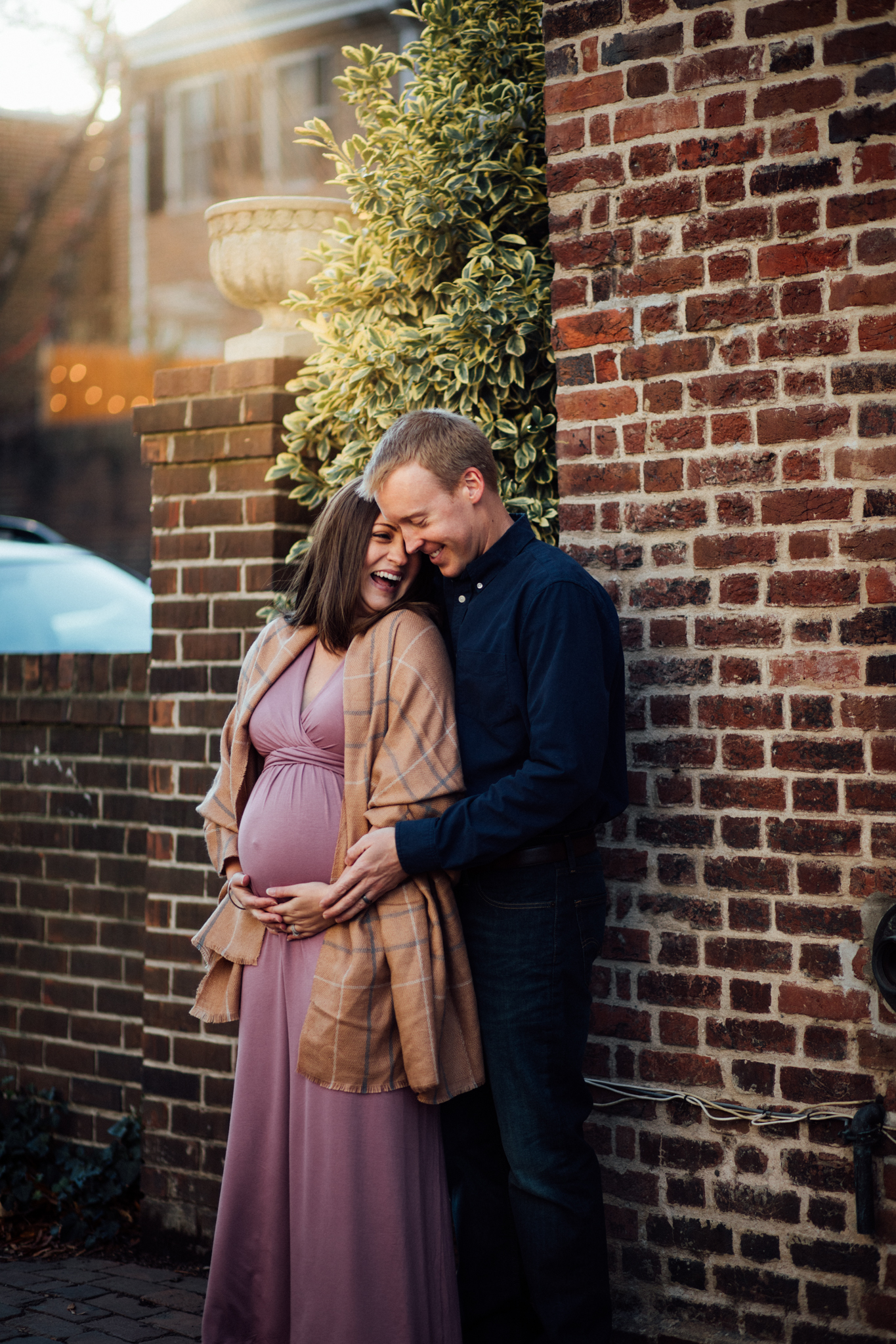Pregnant woman laughing with man in urban setting by Huntsville and Madison Alabama maternity photographer Rachel K Photo