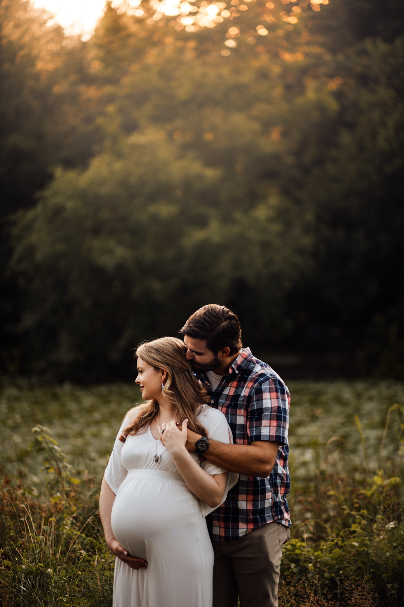Man snuggles pregnant woman in white dress by Huntsville and Madison Alabama maternity photographer Rachel K Photo
