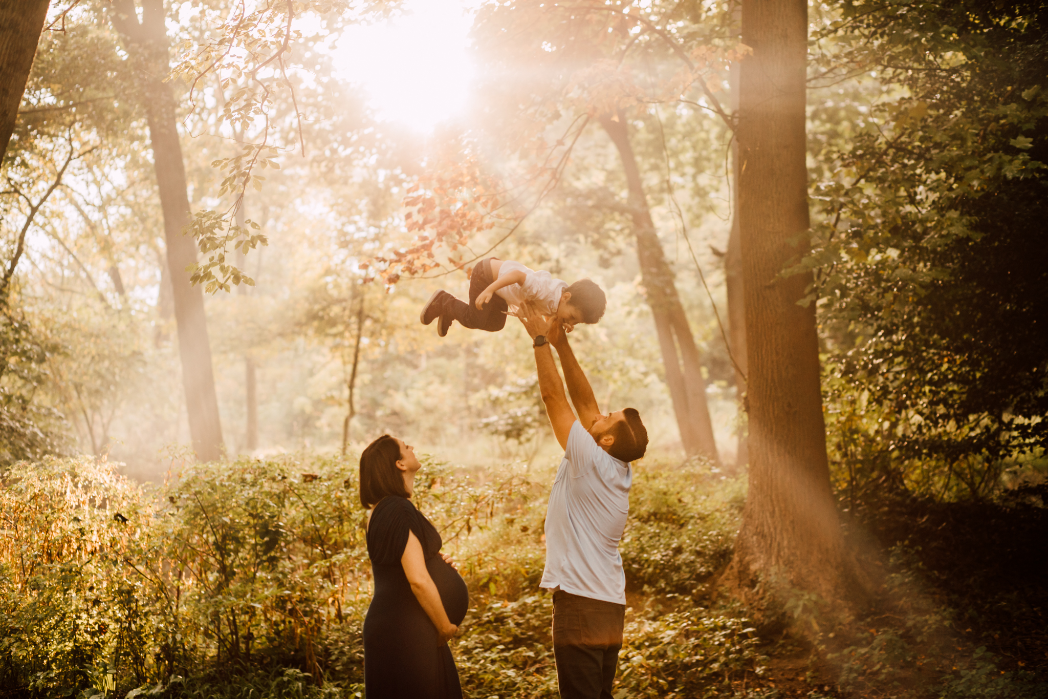 Dad lifts son into air while pregnant mom watches from Huntsville Alabama maternity photographer