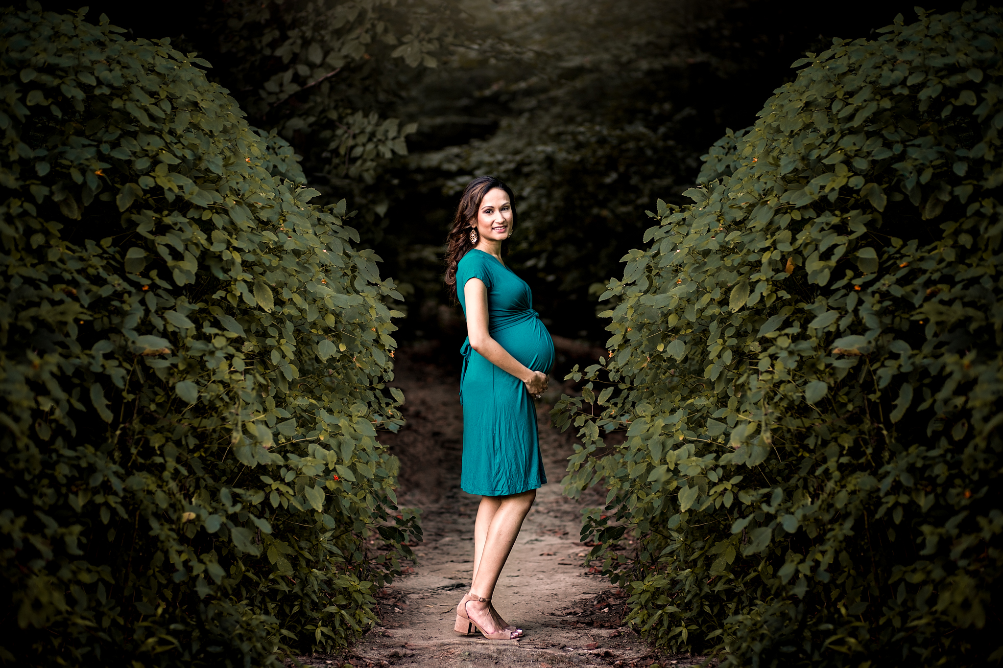 Pregnant woman in teal dress between two bushes by Huntsville and Madison Alabama maternity photographer Rachel K Photo