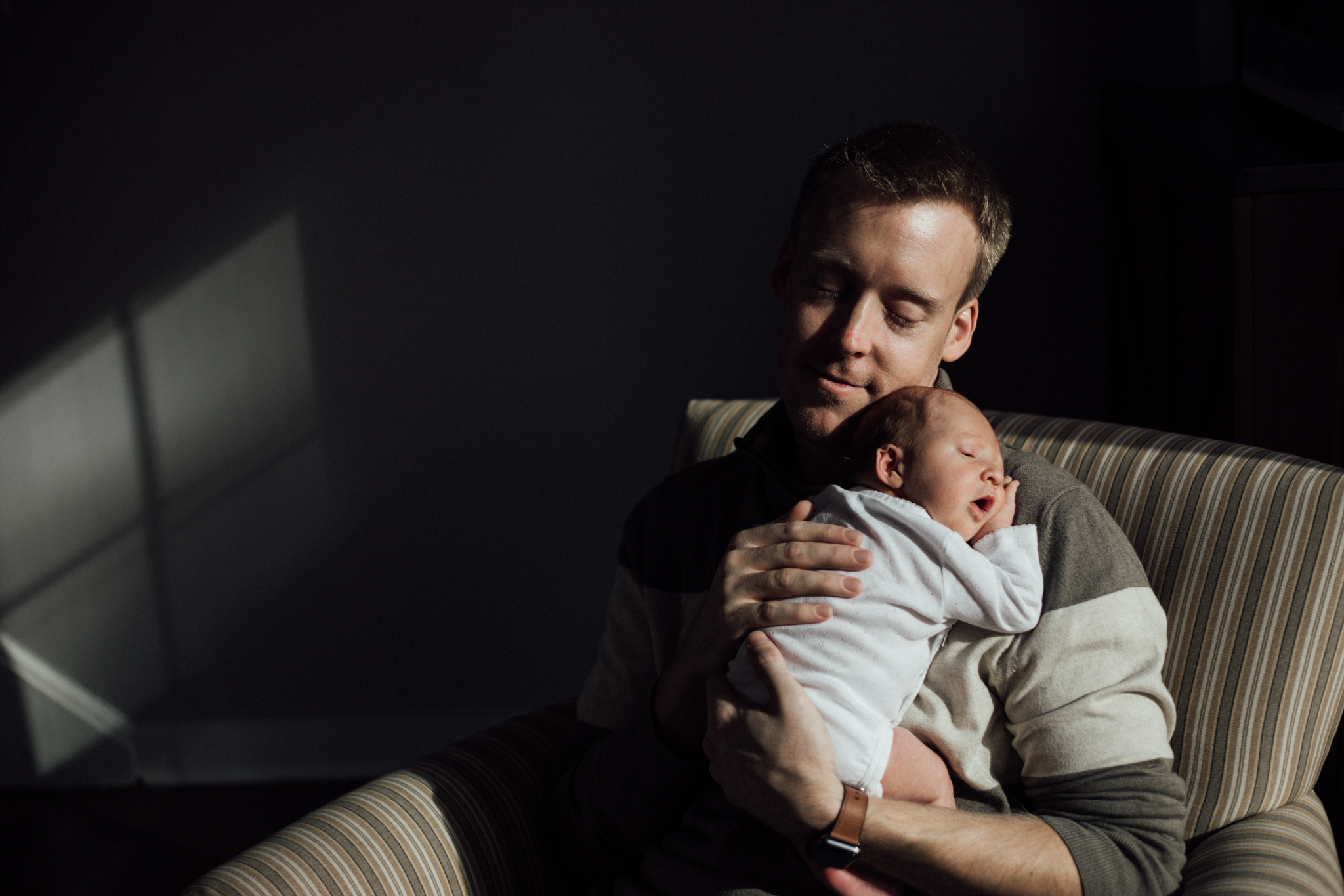 Dad snuggles newborn daughter in chair from Huntsville and Madison Alabama lifestyle newborn photographer Rachel K Photo